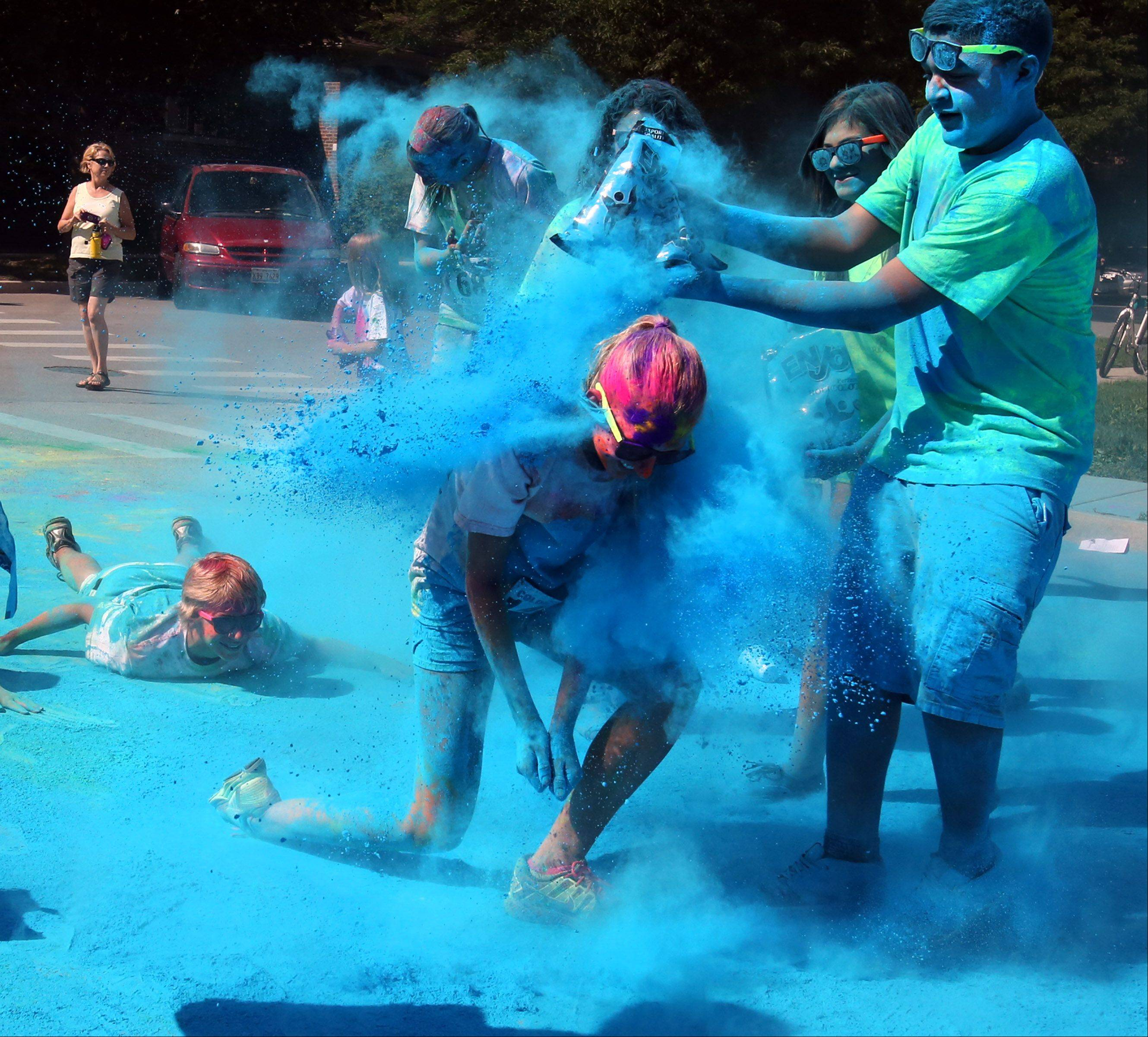 Allie Renner, 13, of Cary, is doused with blue powder by volunteers near the finish of the first Active Care Color Blast 5k run Saturday in Arlington Heights. All proceeds go to Clearbrook.