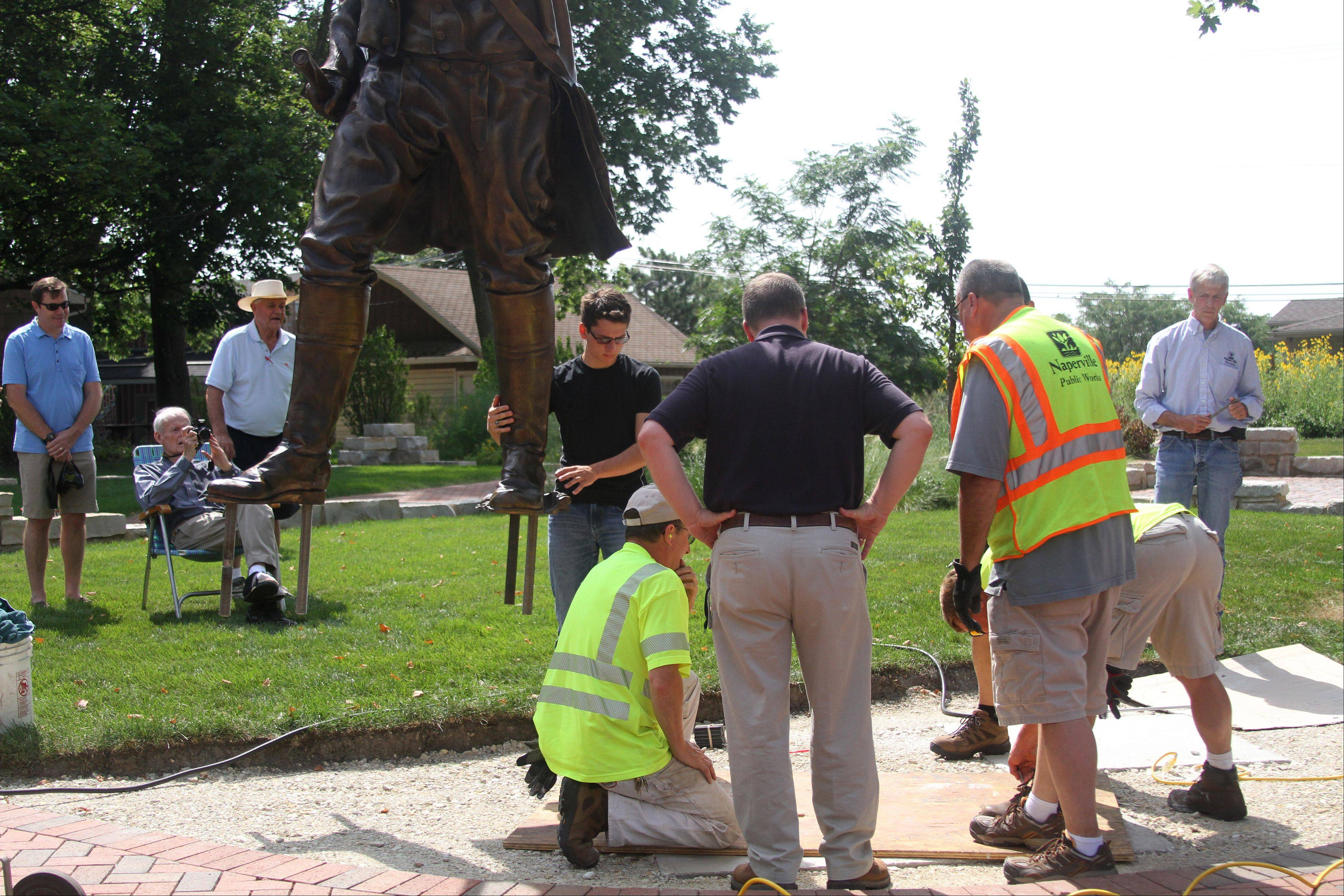 Public works crews drill holes Friday to secure a sculpture of Naperville founder Joseph Naper at the Naper Homestead site near downtown.