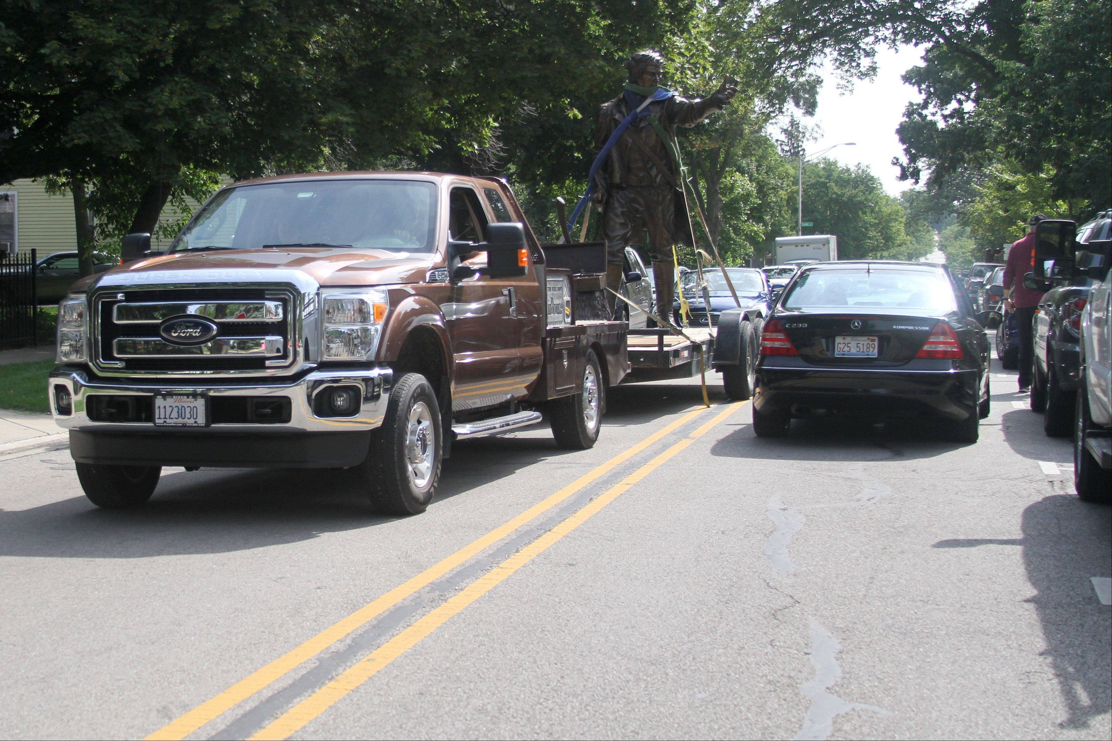 A sculpture of Naperville founder Joseph Naper makes its way Friday down Jefferson Avenue to its home at the Naper Homestead at Jefferson and Mill Street.