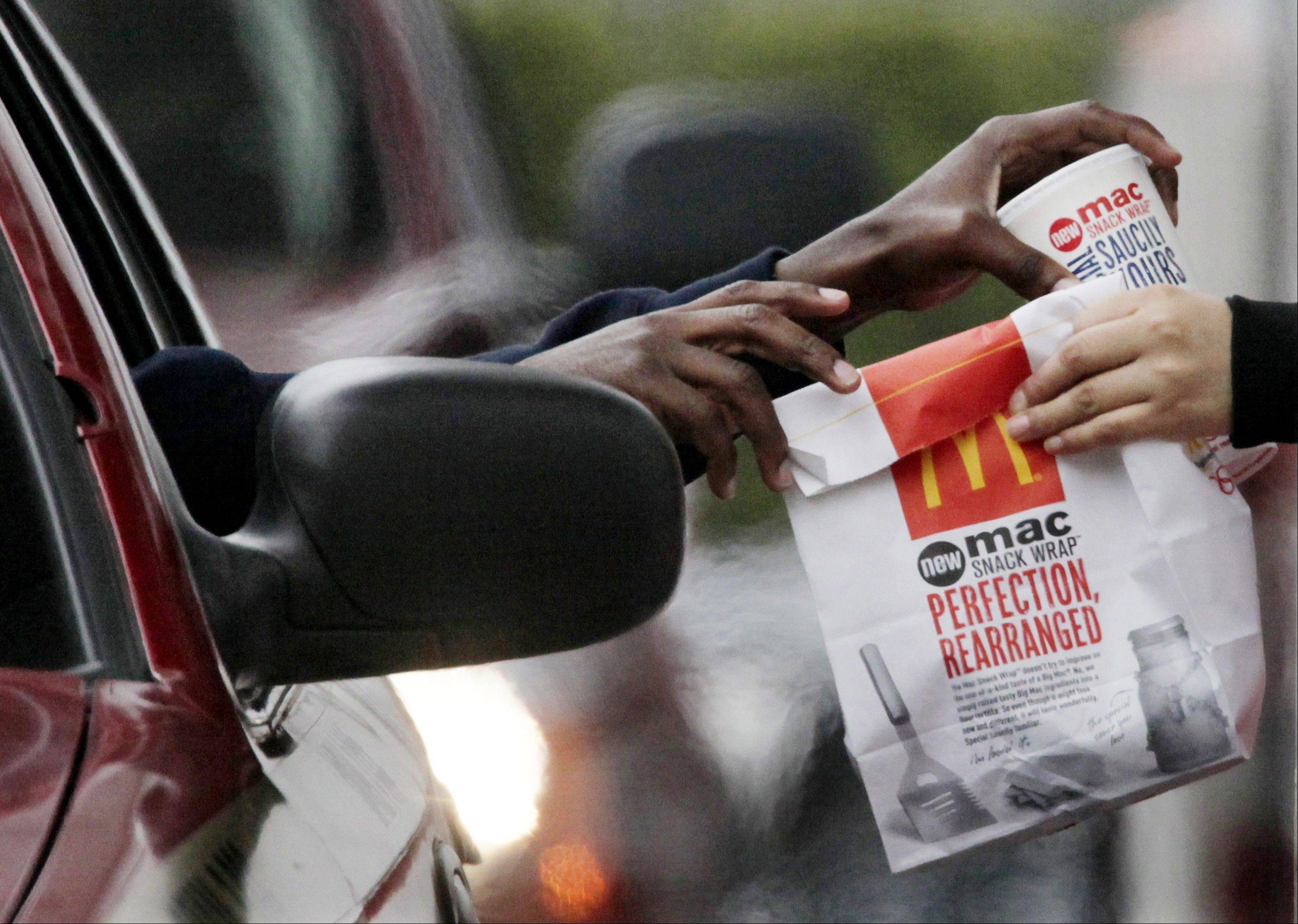 In this Jan. 22, 2010 file photo, a customer grabs lunch at a McDonald's drive-through in Chicago. Fast-food chains such as McDonald's, Burger King and Wendy's are trumpeting pricier, premium offerings to shed their image as purveyors of greasy junk food and convince customers to spend a few extra bucks.
