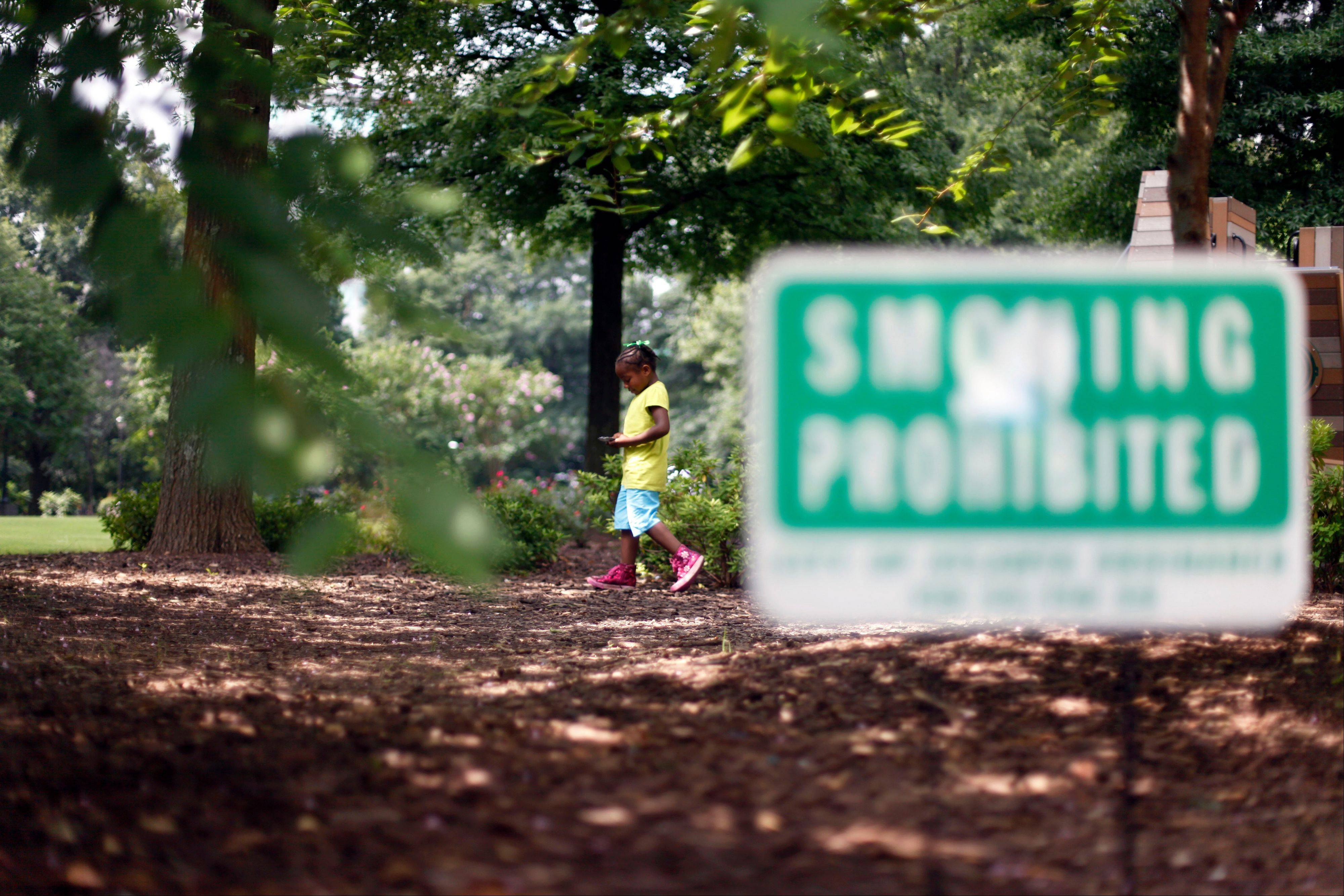 "Ariayanna Stinson, 6, of Atlanta, walks around the playground next to a ""smoking prohibited"" sign in Woodruff Park in Atlanta. ""No Smoking"" signs are going up in parks, beaches and other outdoor venues across the country, but some experts are questioning whether there's enough medical evidence to support the trend."