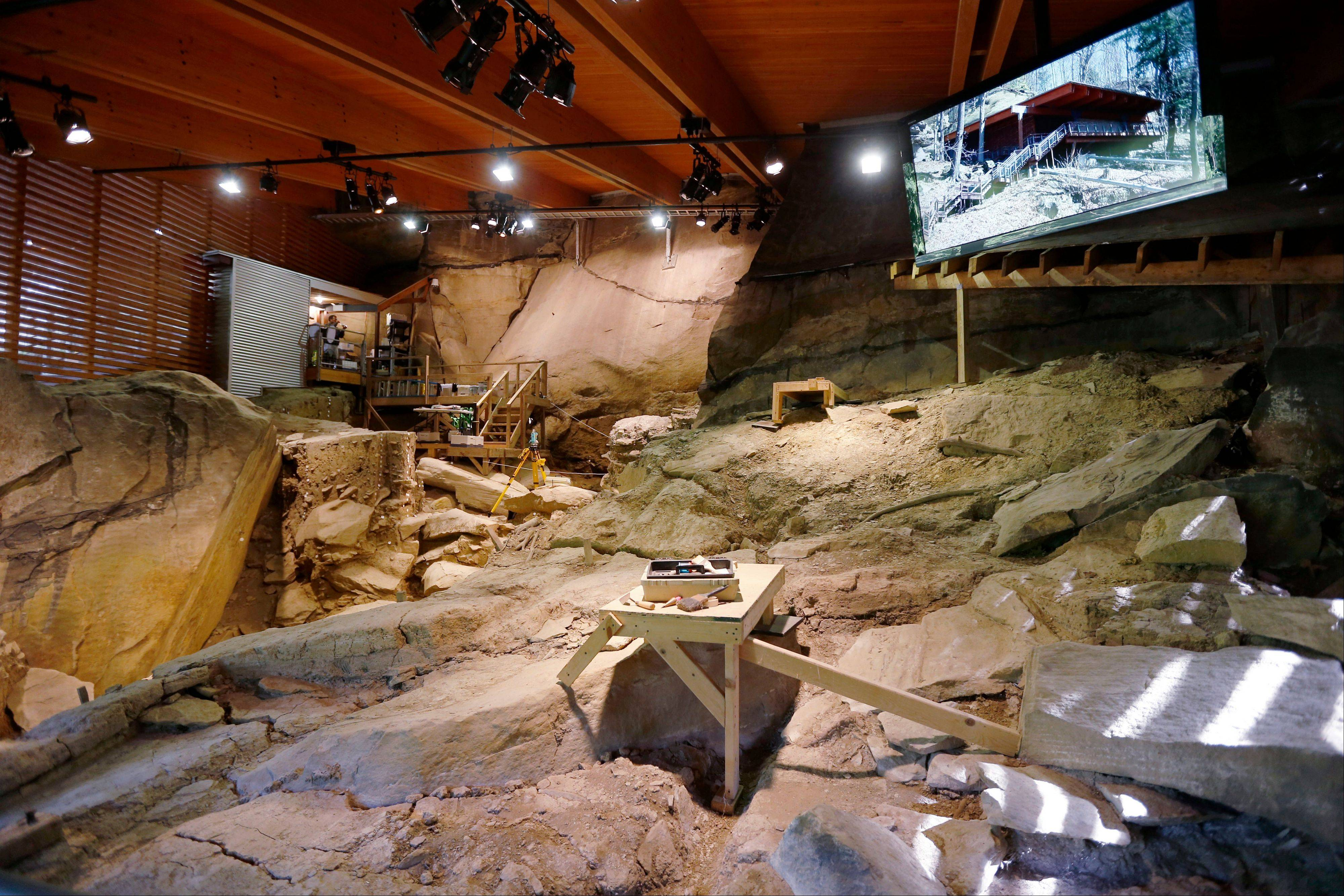 In this Aug. 5 photo, a video display showing the exterior of the shelter is seen is seen above the archeological dig at the Meadowcroft National Historic Site where native Americans stayed as they travelled through the area thousands of years ago in Avella, Pa. A fluke rainstorm has brought Mercyhurst University professor Jim Adovasio back to do new work at the site that launched a furious debate in 1973 over when the first humans came to the Americas.