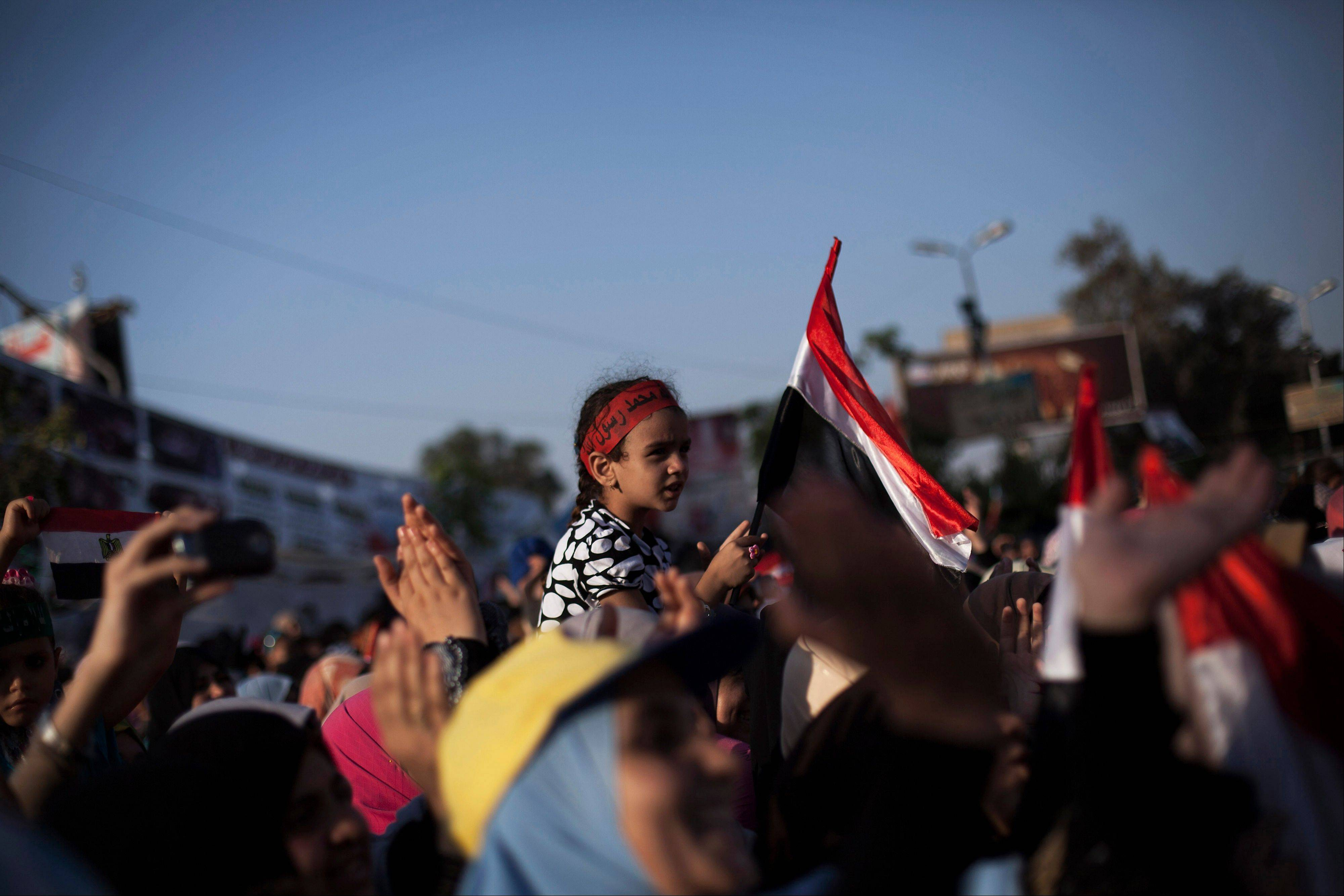 An Egyptian girl waves a national flag while supporters of Egypt's ousted President Mohammed Morsi chant slogans against the Egyptian Army at the sit-in at Rabaah al-Adawiya mosque, which is fortified with multiple walls of bricks, tires, metal barricades and sandbags, and where protesters have installed their camp in Nasr City, Cairo, Egypt, Sunday, Aug. 11, 2013. Egyptian security forces will besiege two sit-ins by supporters of the country's ousted president within 24 hours, police officials said Sunday, setting up a possible confrontation between the military-backed government and the thousands gathered there.