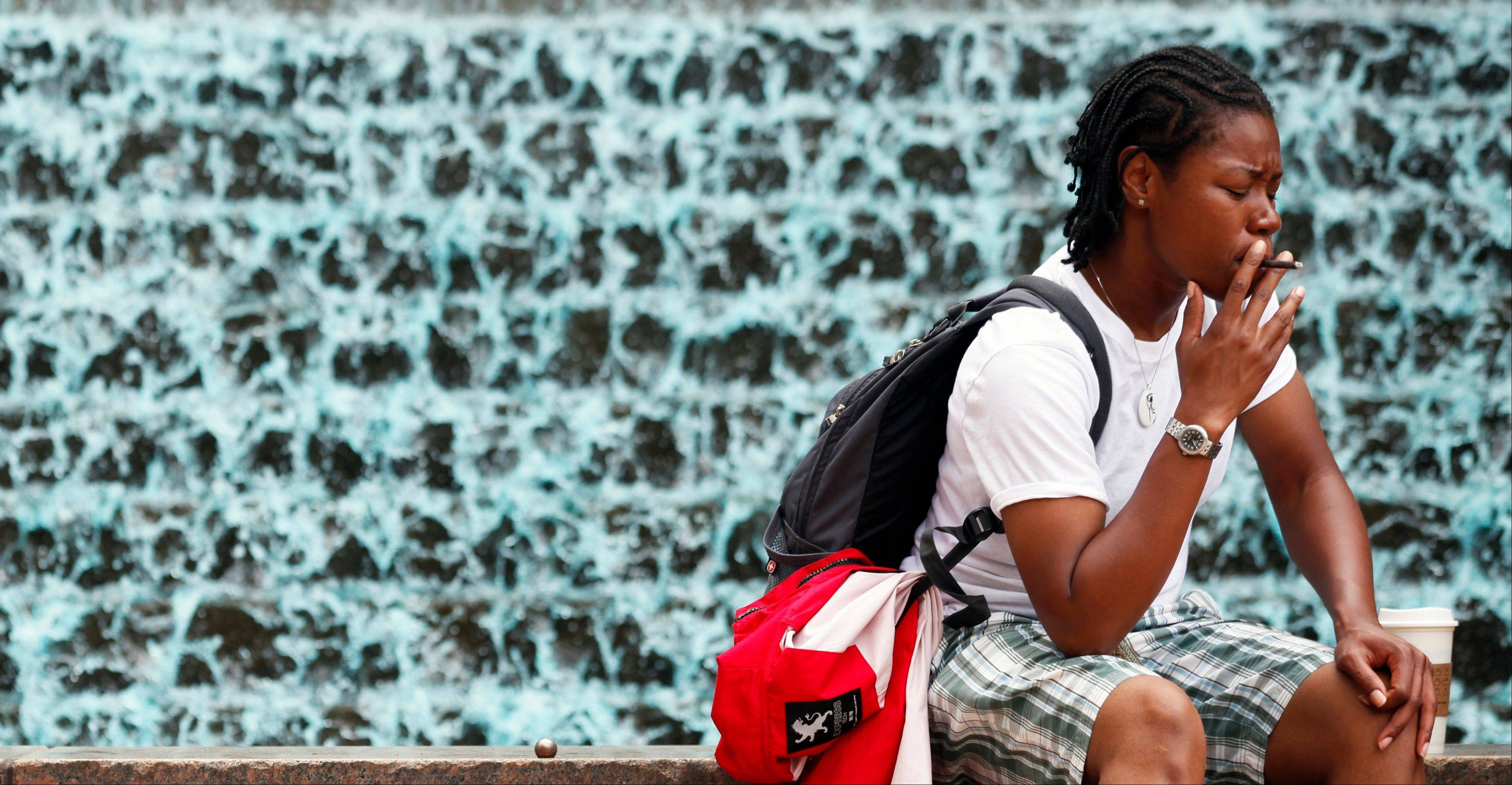 Venisha Smalls, 35, of Atlanta, takes a smoke break next to a fountain in Woodruff Park in Atlanta.