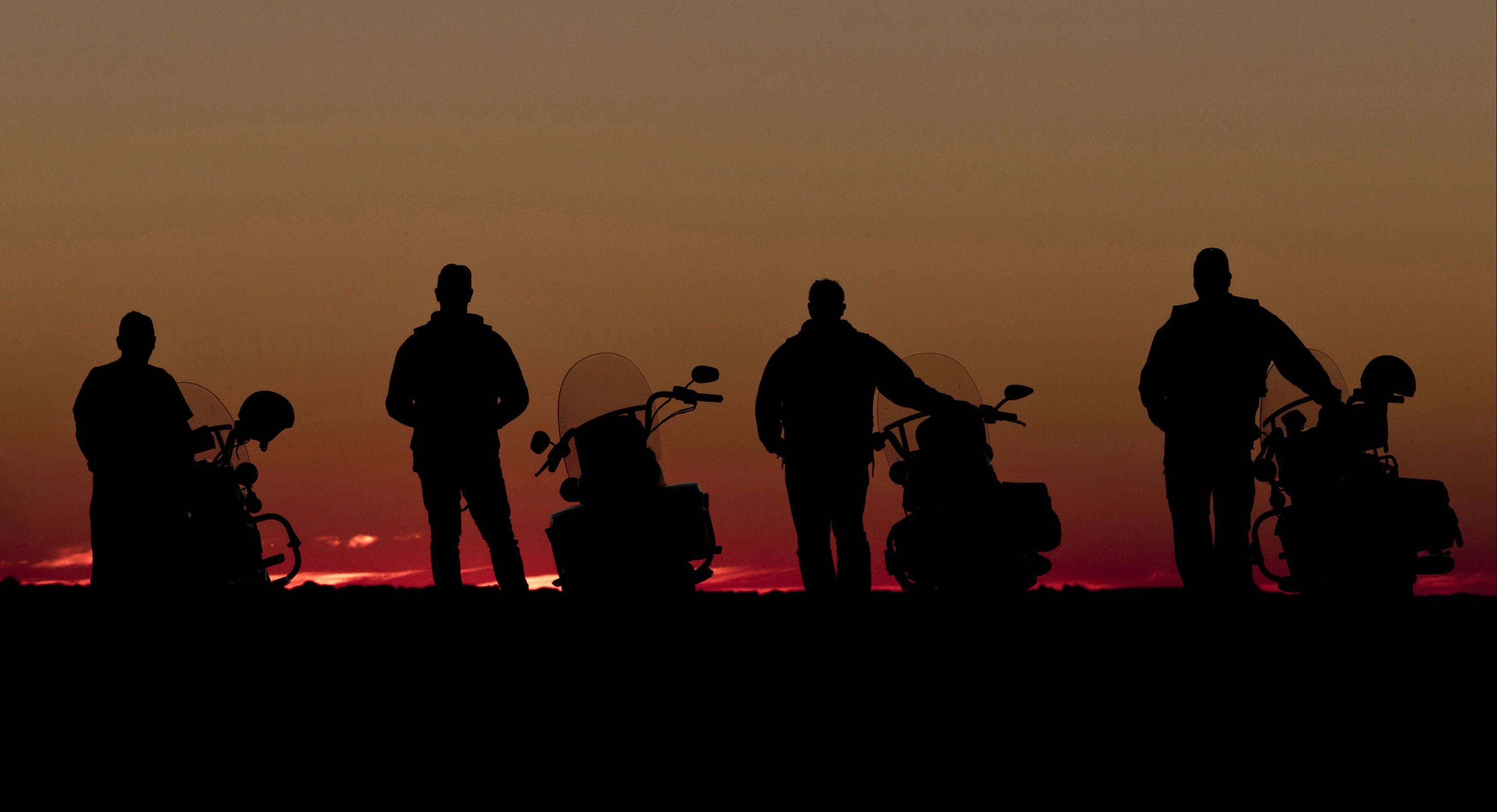 Four riders stand next to their motorcycles and watch the sun set near Broken Hill, Australia.