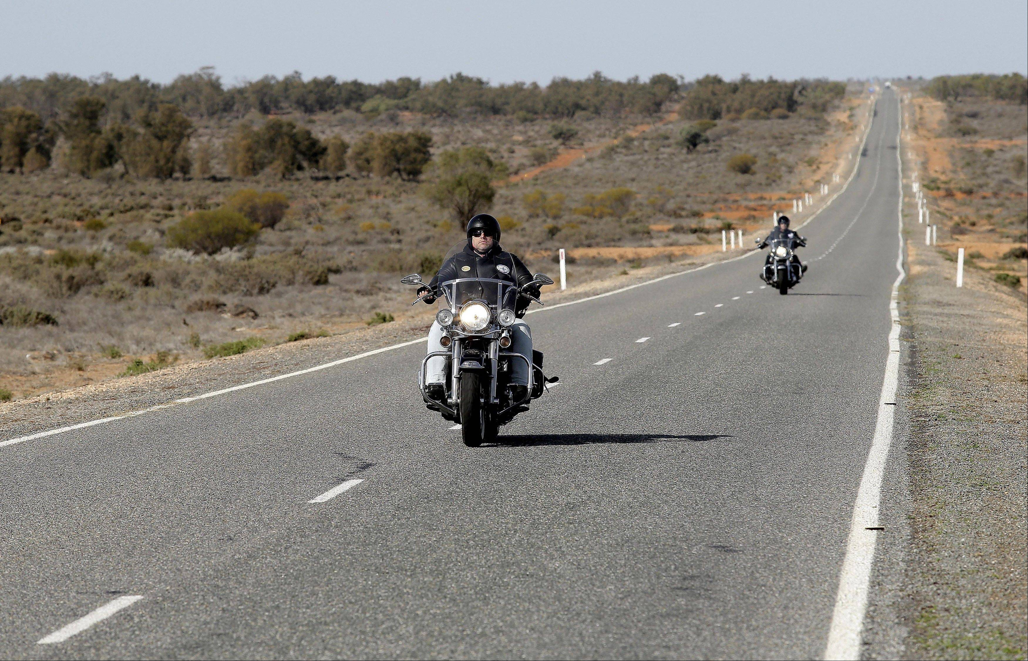Motorcyclists pass along a long straight stretch of the Silver City Highway in Australia's Outback.