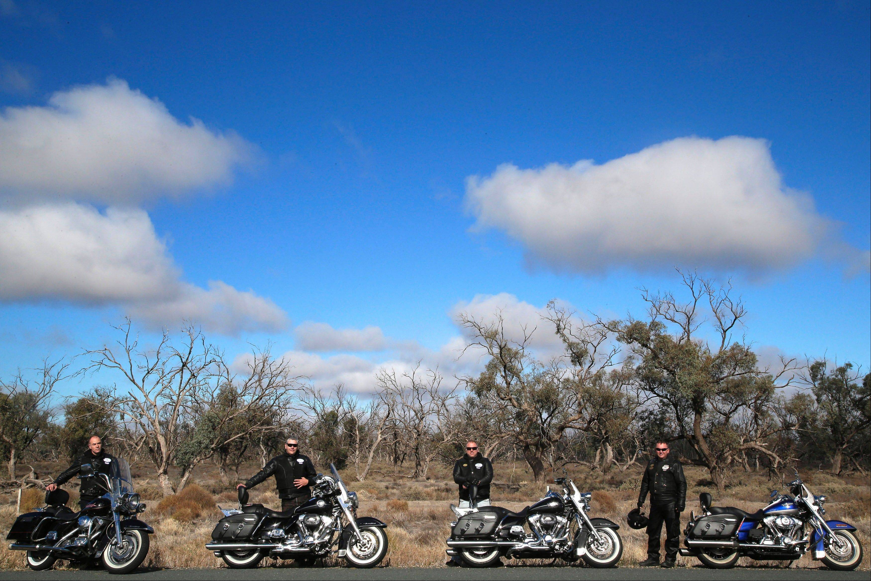Motorcycle tourists, from left, John Roe, Rob Griffith, Glenn Nicholls and Stefan Hersee rest on the roadside near Wentworth, Australia.