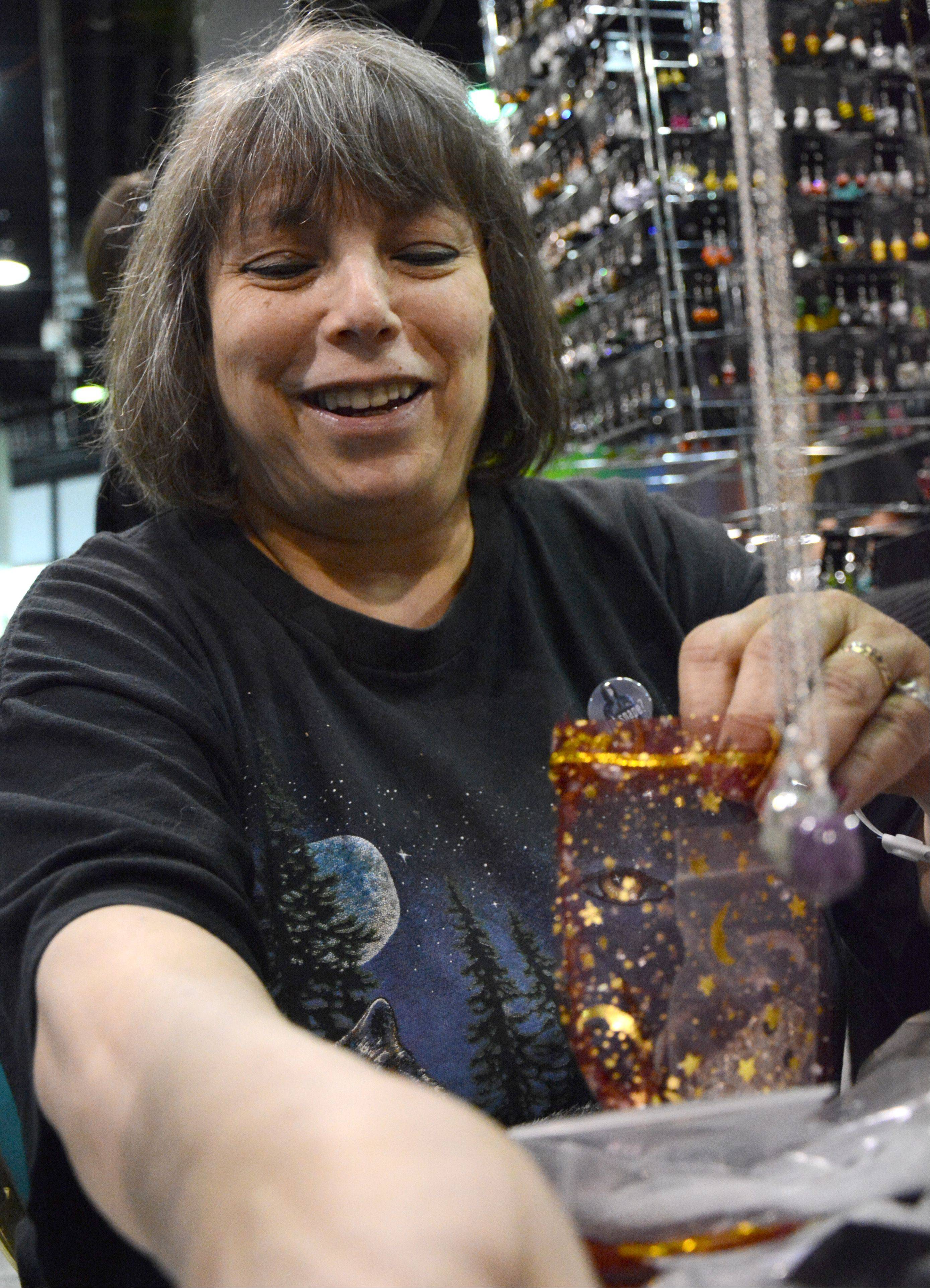 Merrilyn Greenfield, of Northbrook, bags jewelry for a customer during Wizard World Chicago Comic Con in Rosemont Sunday.