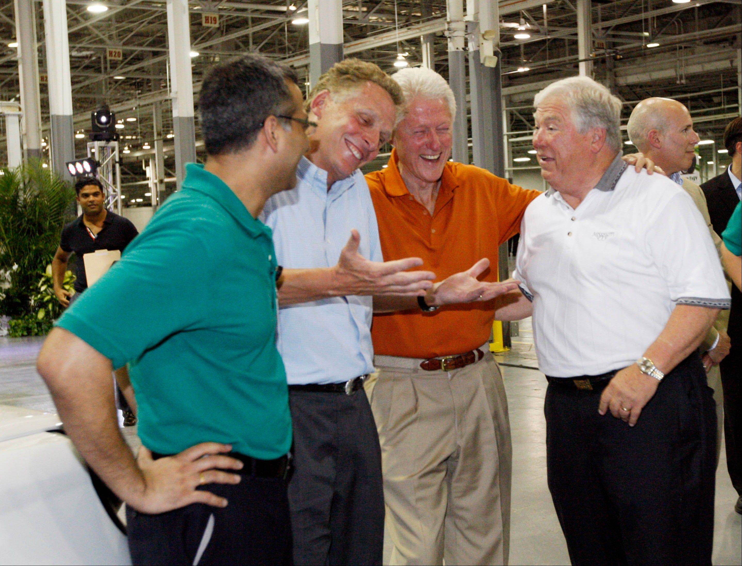 In this July 6, 2012, file photograph, then GreenTech Automotive executive Terry McAuliffe, second from left, jokes with former President Bill Clinton, center and former Mississippi Gov. Haley Barbour following the unveiling of their new electric MyCar at their manufacturing facility in Horn Lake, Miss. The big plans of eventually hiring a workforce of 25,000 people and eventually producing 1 million cars a year have been scaled back to a smaller facility to make 30,000 electric vehicles a year.