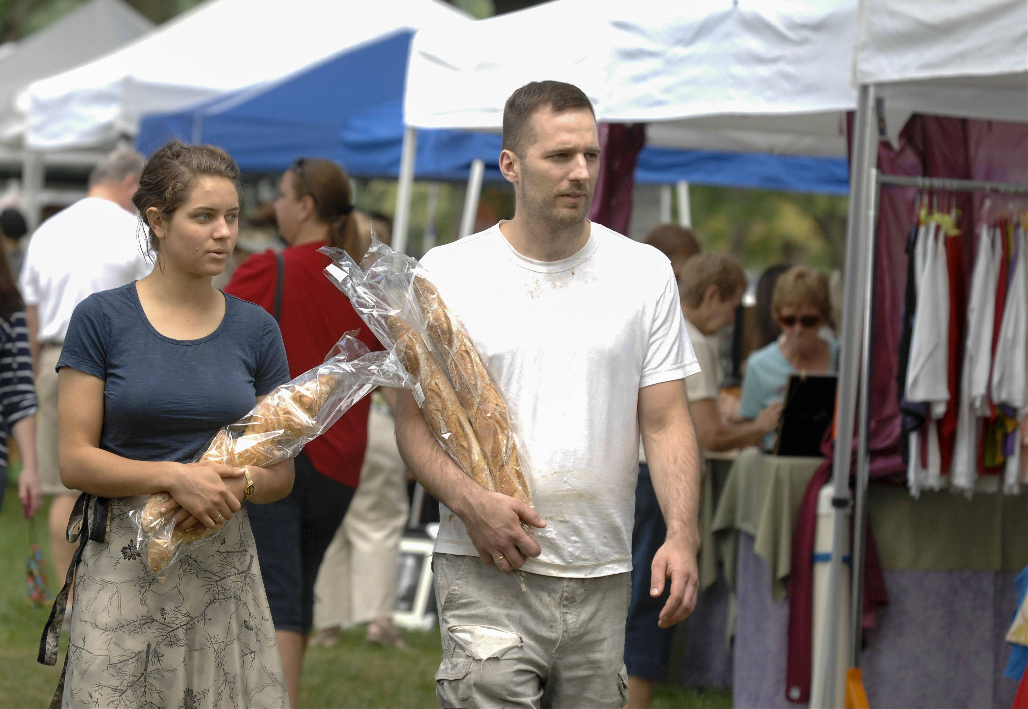 Carissa and Dusan Katic carry two different kinds of French breads they purchased at the French market Sunday at Cantigny Park's French Connection Day in Wheaton.