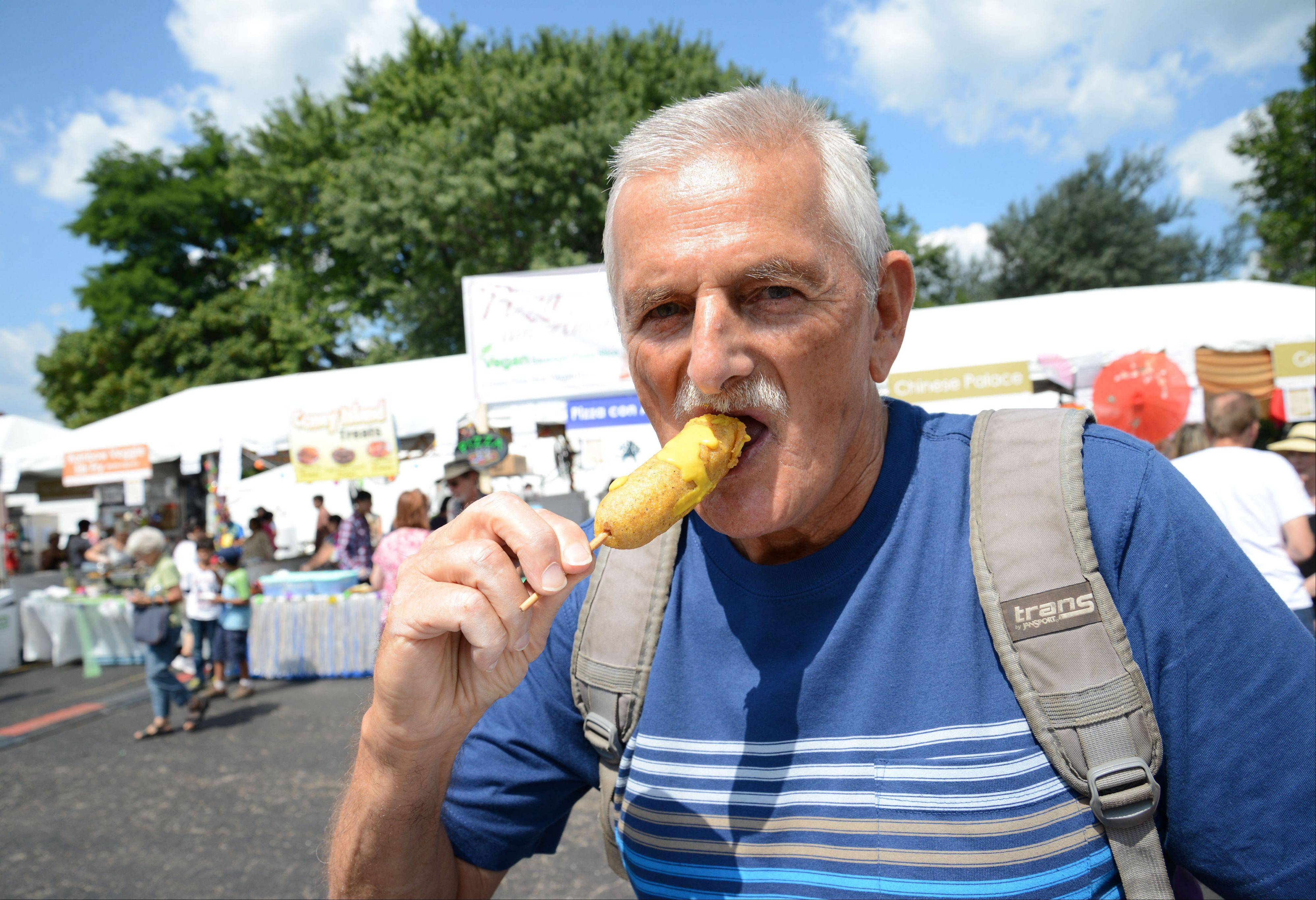 John Servidio, of Naperville, enjoys a veggie dog Saturday during the eighth annual Veggie Fest at Science of Spirituality Meditation Center in Naperville. The event continues Sunday.