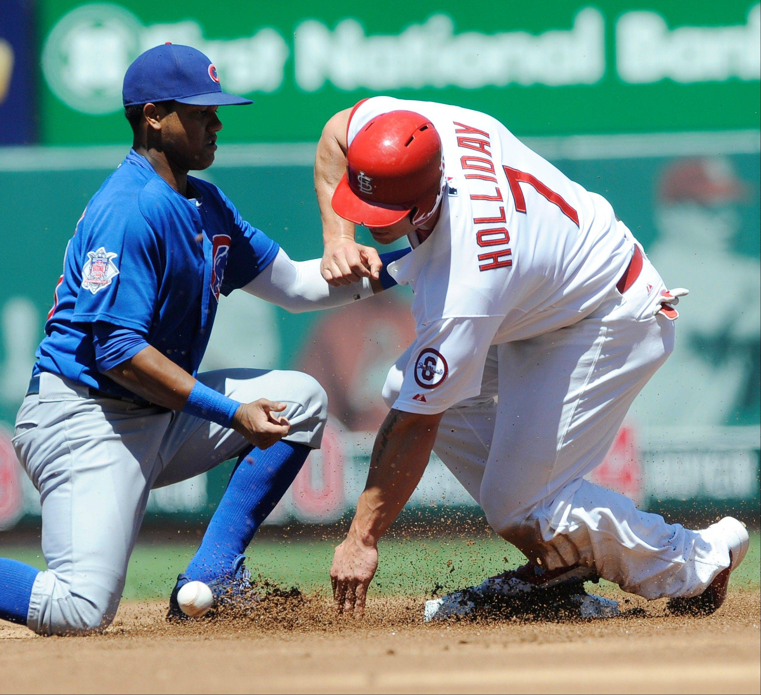 The St. Louis Cardinals' Matt Holliday steals second as the Cubs' Starlin Castro, left, cannot make the tag in Sunday's first inning at Busch Stadium.