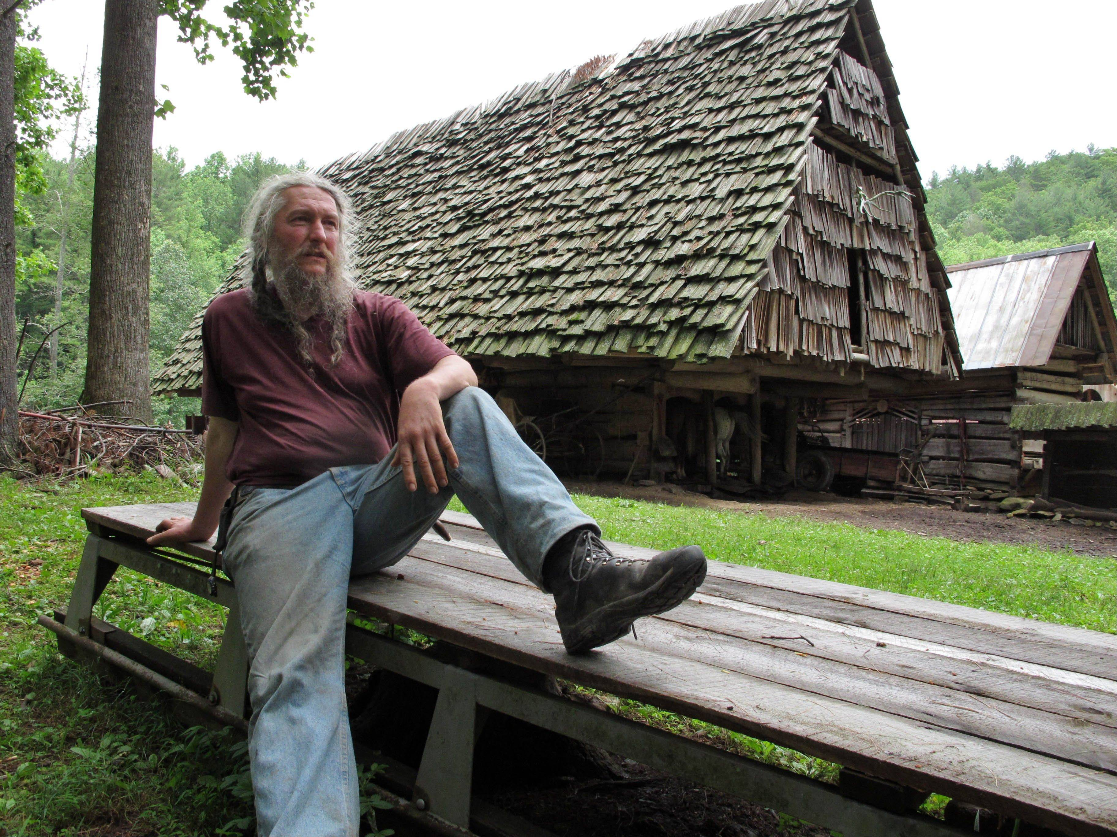Eustace Conway rests on a wooden sledge in front of the horse barn at his Turtle Island Preserve in Triplett, N.C. People come from all over the world to learn natural living and how to go off-grid, but local officials ordered the place closed over health and safety concerns.