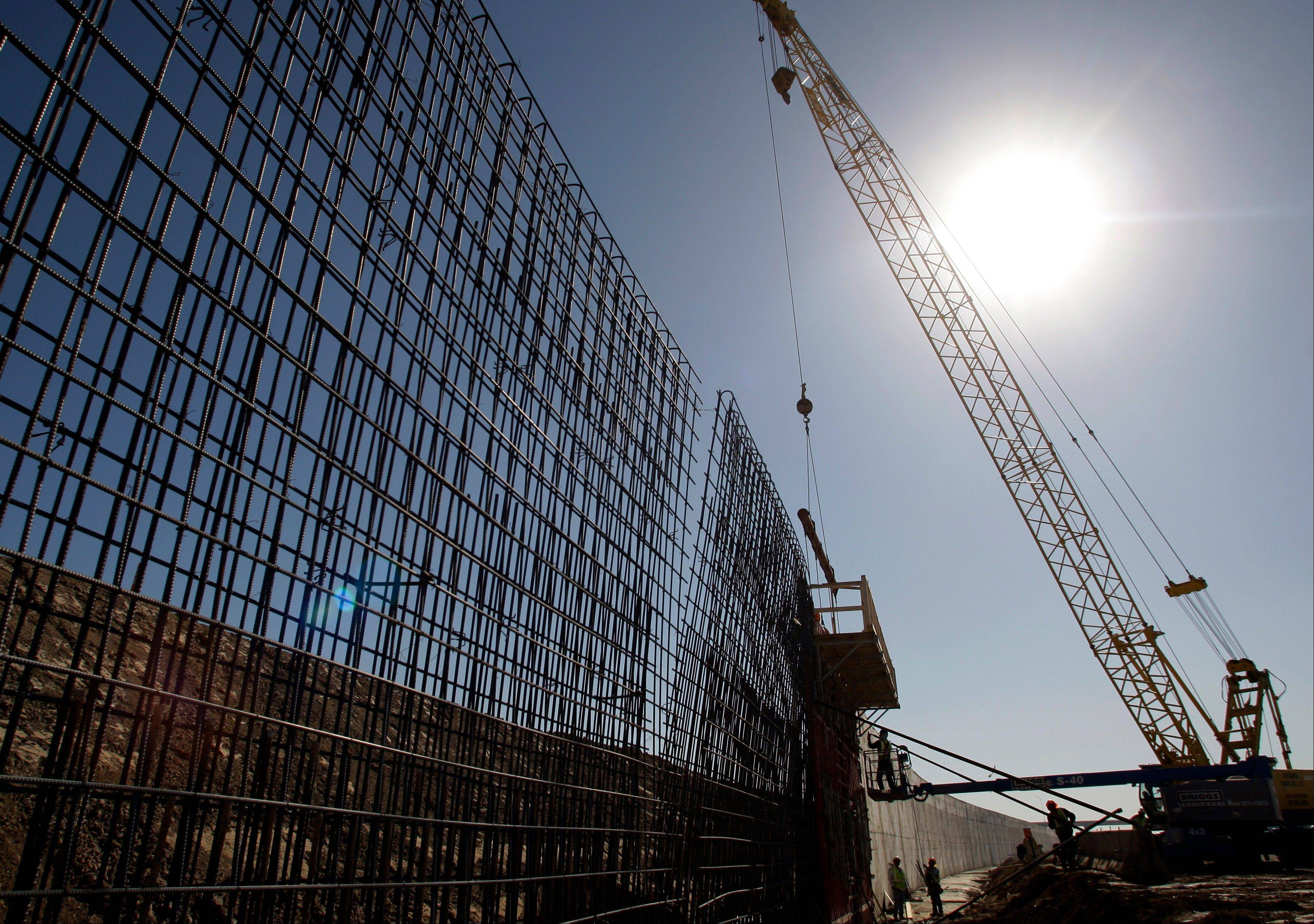 In this Feb. 4, 2009 file photo, the sun beats down on construction workers constructing the border wall in Granjeno, Texas. If Congress agrees on a comprehensive immigration reform bill, it will probably include a requirement to erect fencing that would wrap more of the nation�s nearly 2,000-mile Southwest border in tall steel columns.