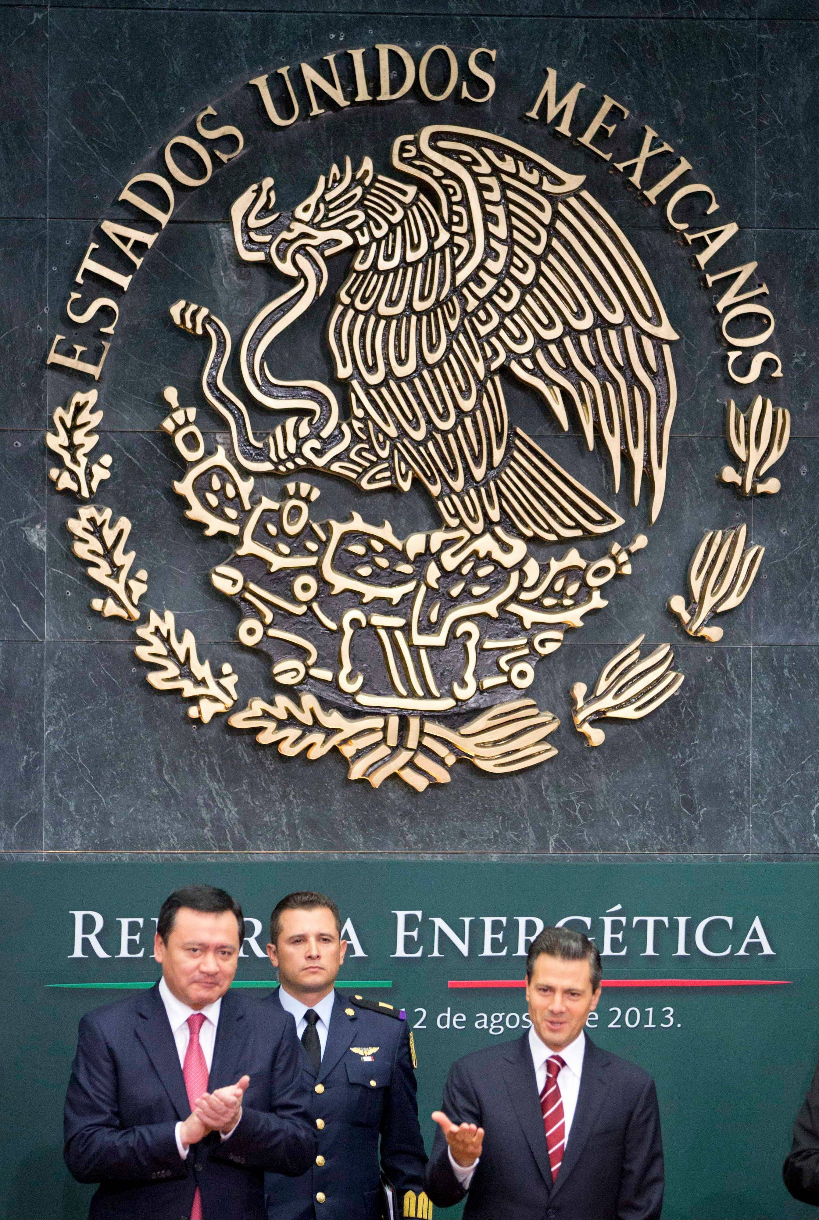 Mexico�s President Enrique Pena Nieto, right, greets the audience as his Interior Secretary Miguel Angel Osorio Chong, left, applauds upon his arrival to the ceremony to announce his proposal that would allow private firms in the oil industry in Mexico City, Monday, Aug. 12, 2013. Pena Nieto is making his most daring gamble yet, with a proposal to lift a decades-old ban on private companies in the state-run oil industry, a cornerstone of Mexico�s national pride.