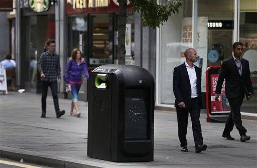 People walk past a trash bin in central London, Monday. Officials say that an advertising firm must immediately stop using its network of high-tech trash cans, like this one, to track people walking through London's financial district.
