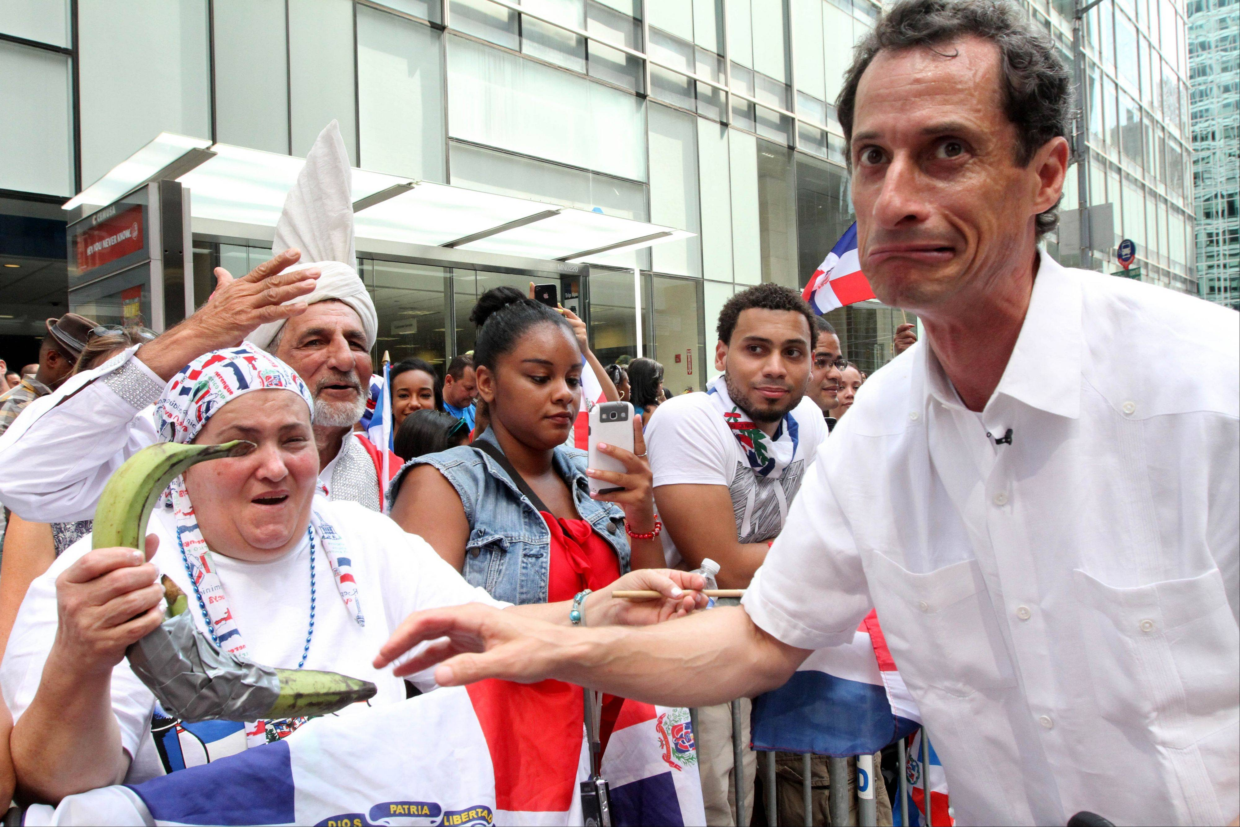 Anthony Weiner, running in the New York Mayors race, right, reacts after sharing a moment with a spectator and her plantains, left, as he takes part in the Dominican Day Parade on New York�s Avenue of the Americas Sunday.