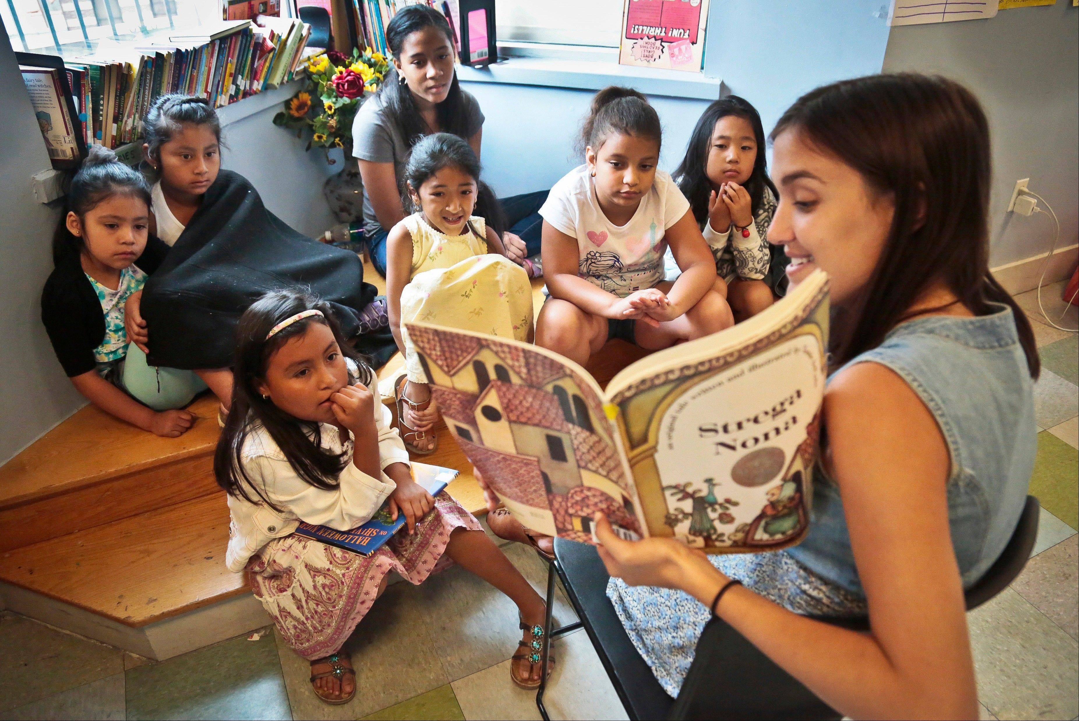 Sophie Mortner, foreground right, reads aloud for youngsters attending LitCamp, a summer reading program offered through the nonprofit literacy organization LitWorld, in the Harlem neighborhood of New York.