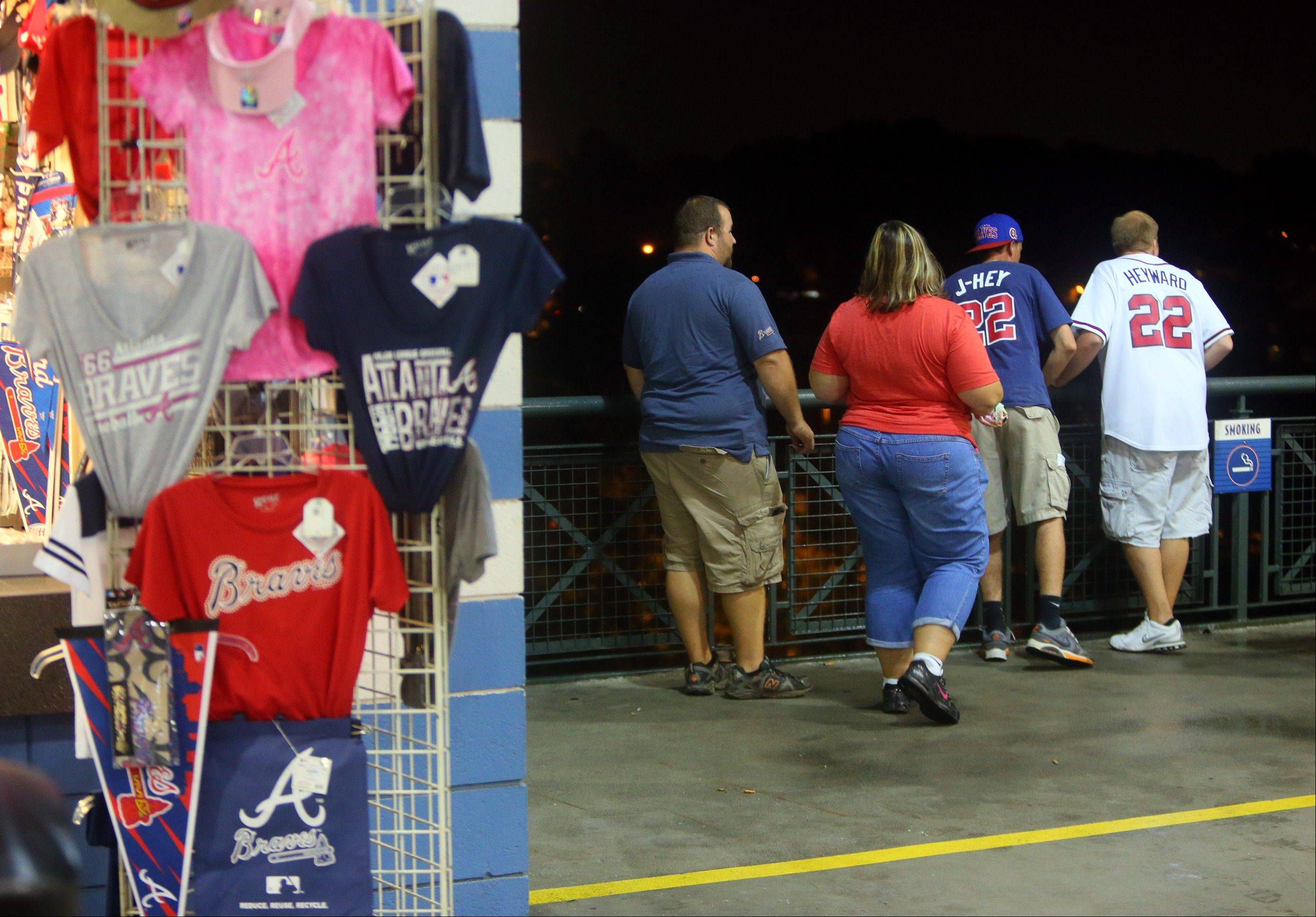 Baseball fans look over a railing at Turner Field near the scene where a man fell 65 feet to his death Monday in Atlanta.