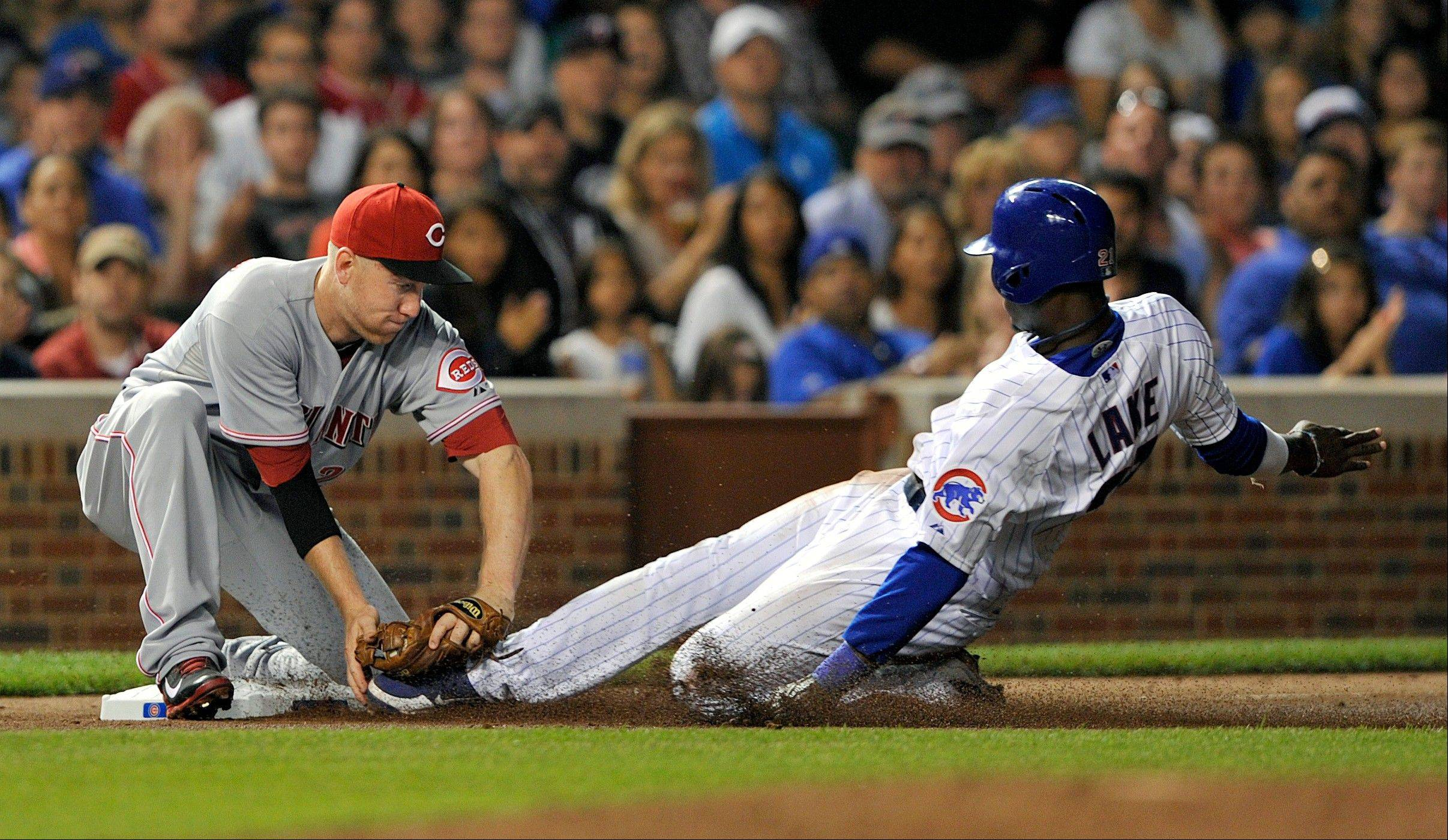 Cincinnati's Todd Frazier tags out the Cubs' Junior Lake at third base after a single by Anthony Rizzo during the sixth inning Monday at Wrigley Field.