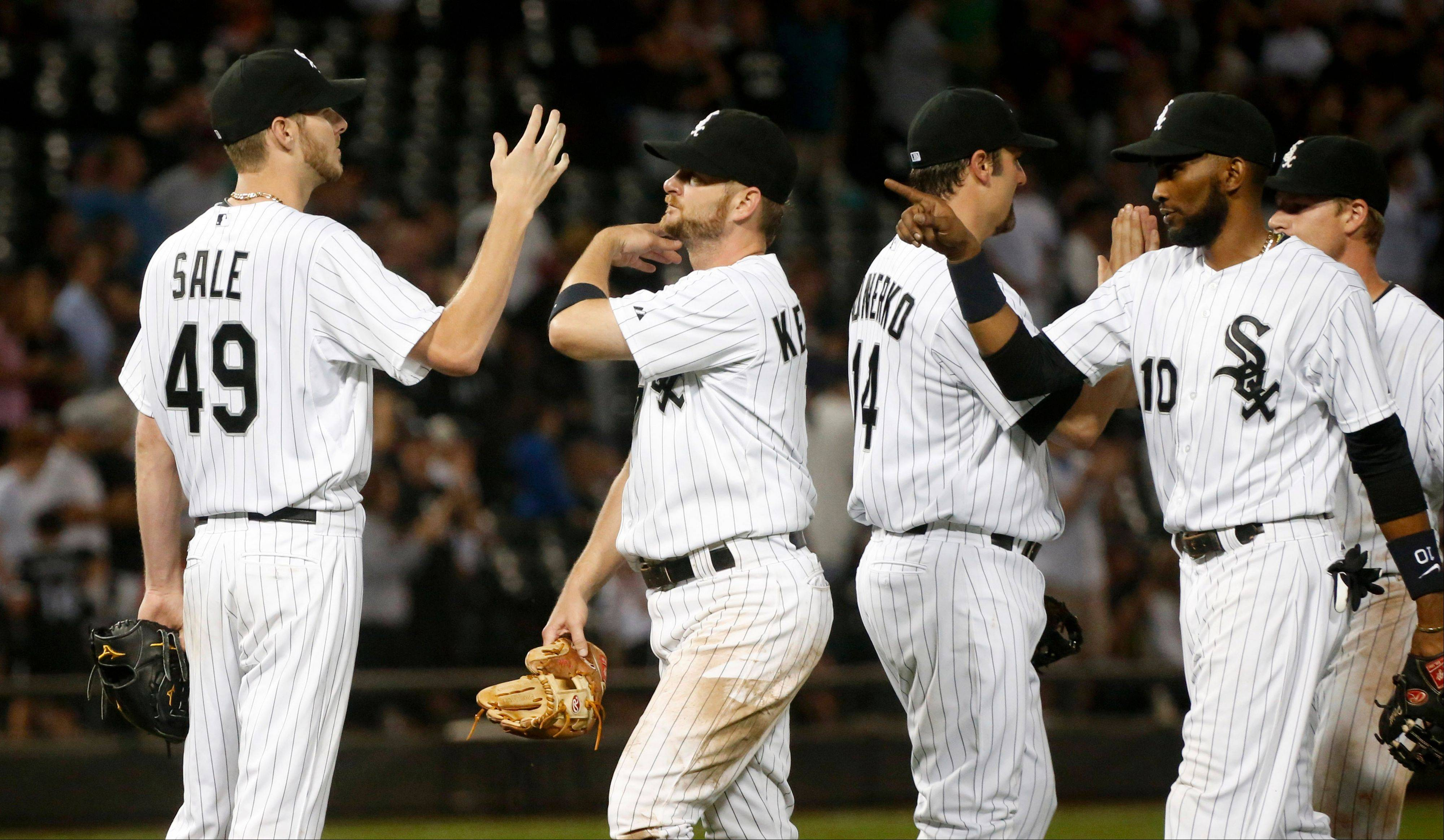 White Sox starting pitcher Chris Sale, left, celebrates his complete game win over the Tigers with Jeff Keppinger, center and Alexei Ramirez on Monday at U.S. Cellular Field.