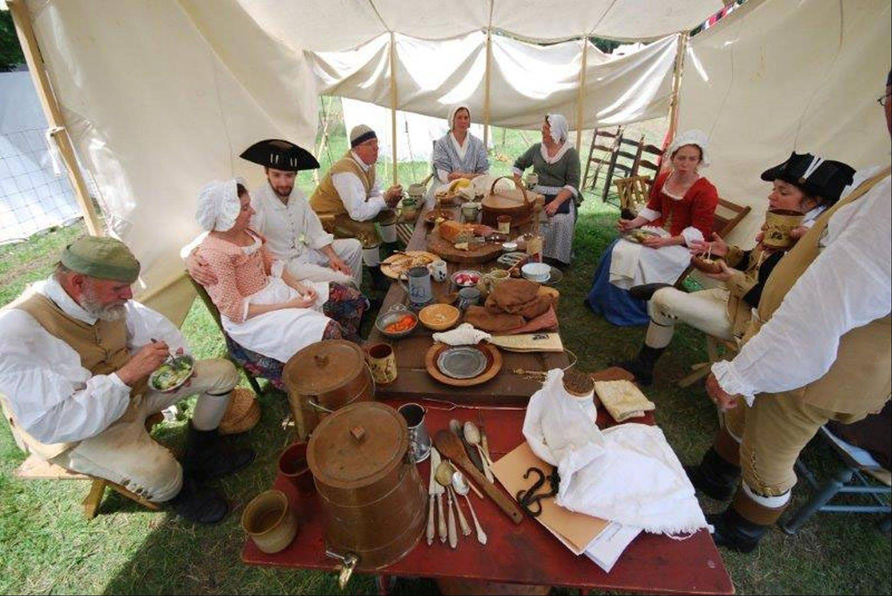 A group of re-enactors eat together at a Revolutionary War camp site.