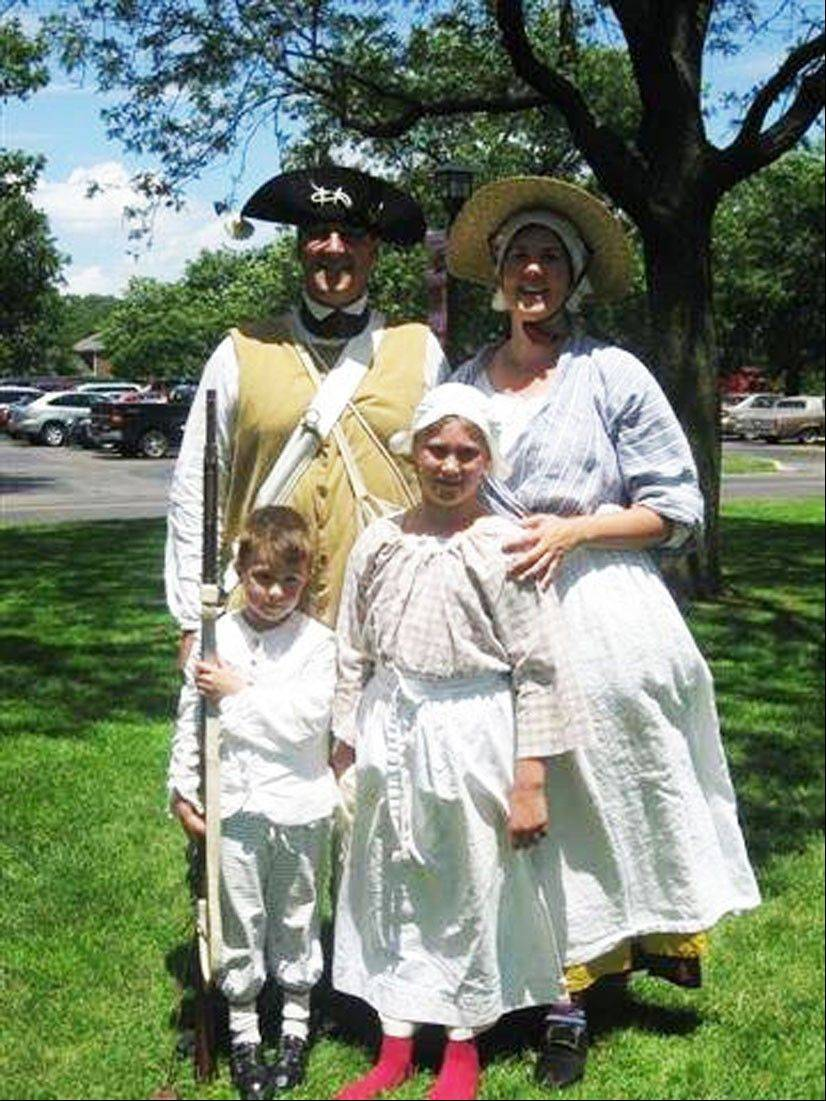 Keith Gill and his wife, Christine, pose for a photo during a re-enactment with their two children, William, left, and Valerie.