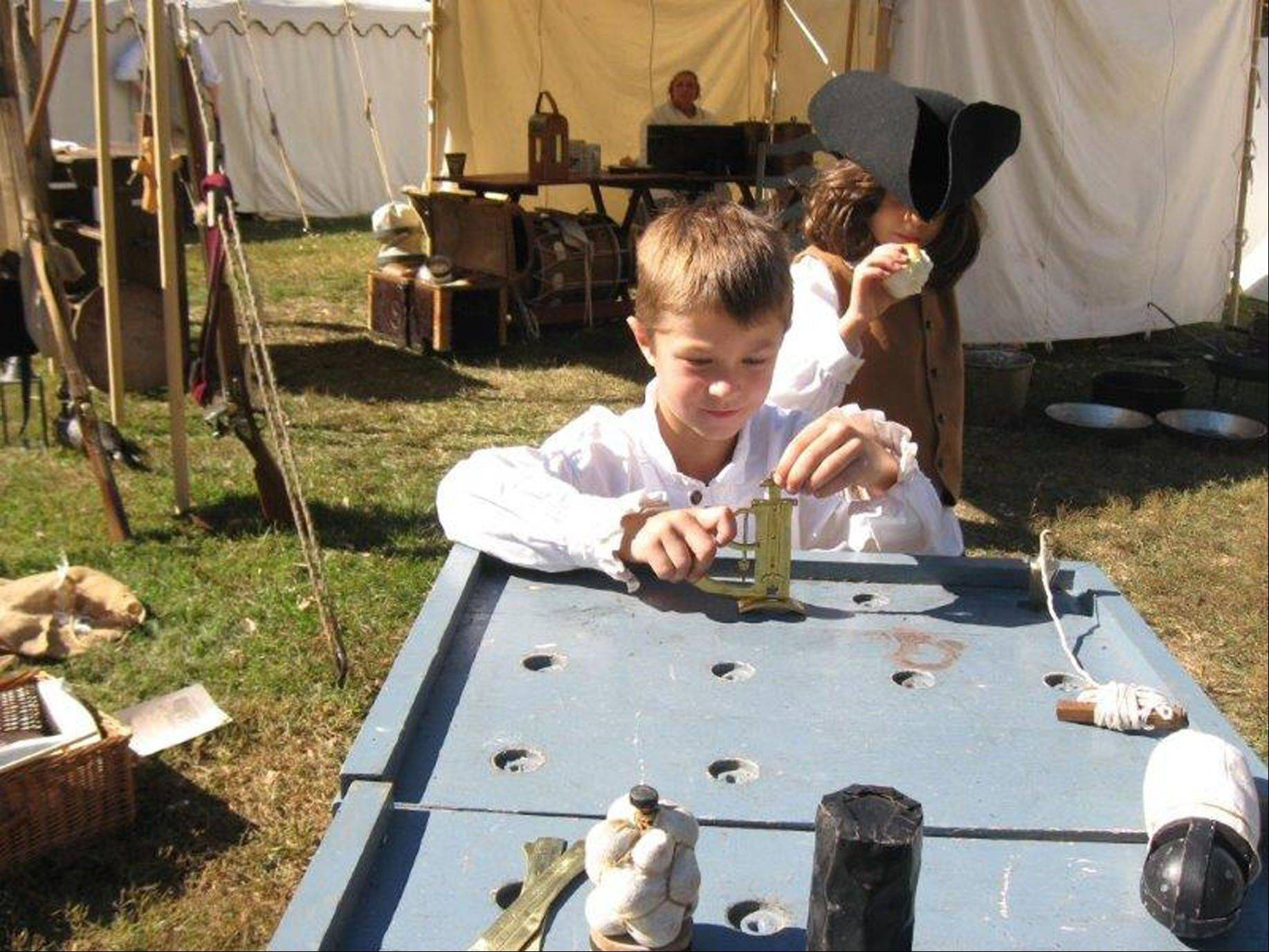 William Gill, 8, must entertain himself at re-enactment campsites by playing period games. He shows young visitors how the games are played.