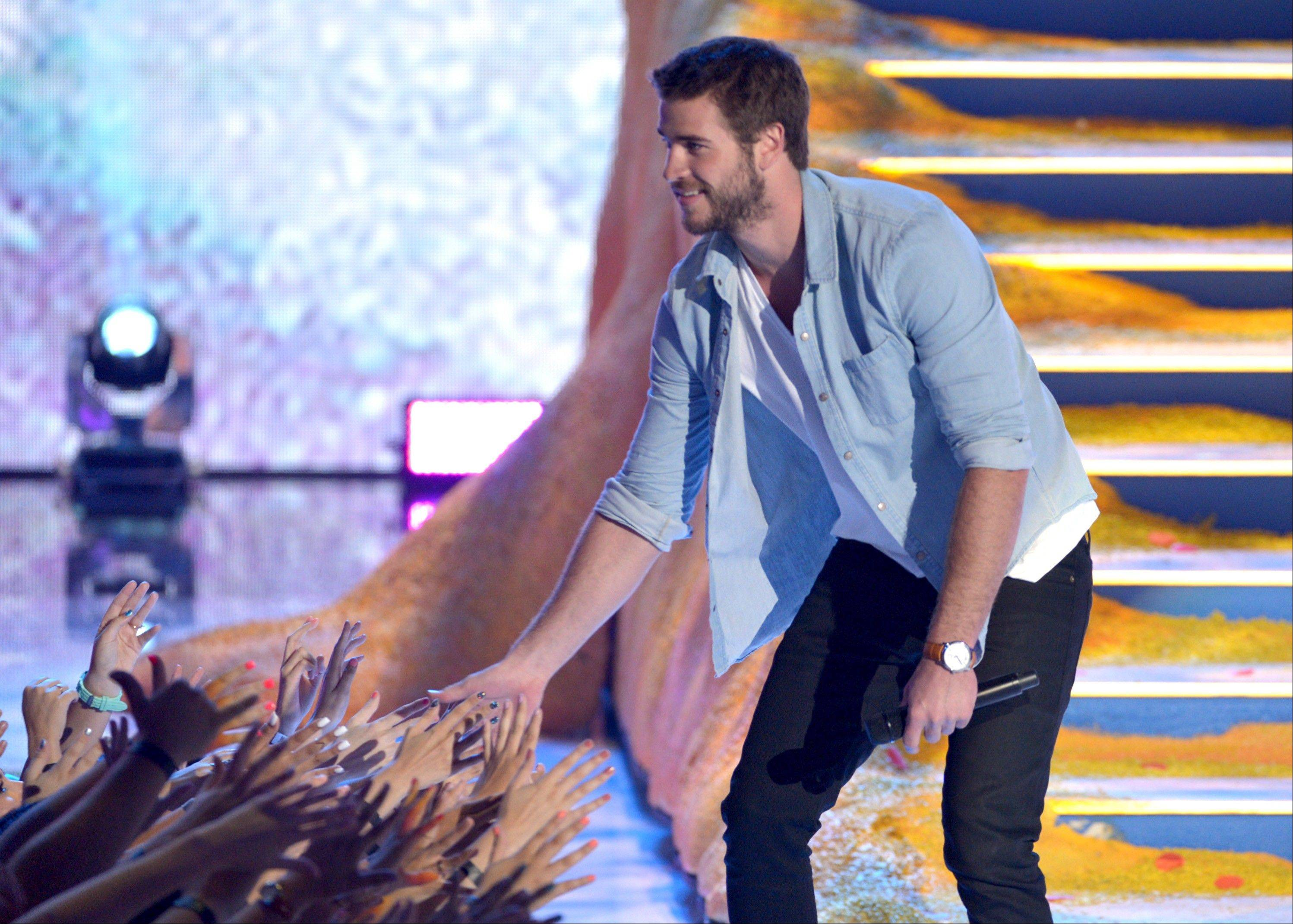 Presenter Liam Hemsworth speaks on stage at the Teen Choice Awards at the Gibson Amphitheater.