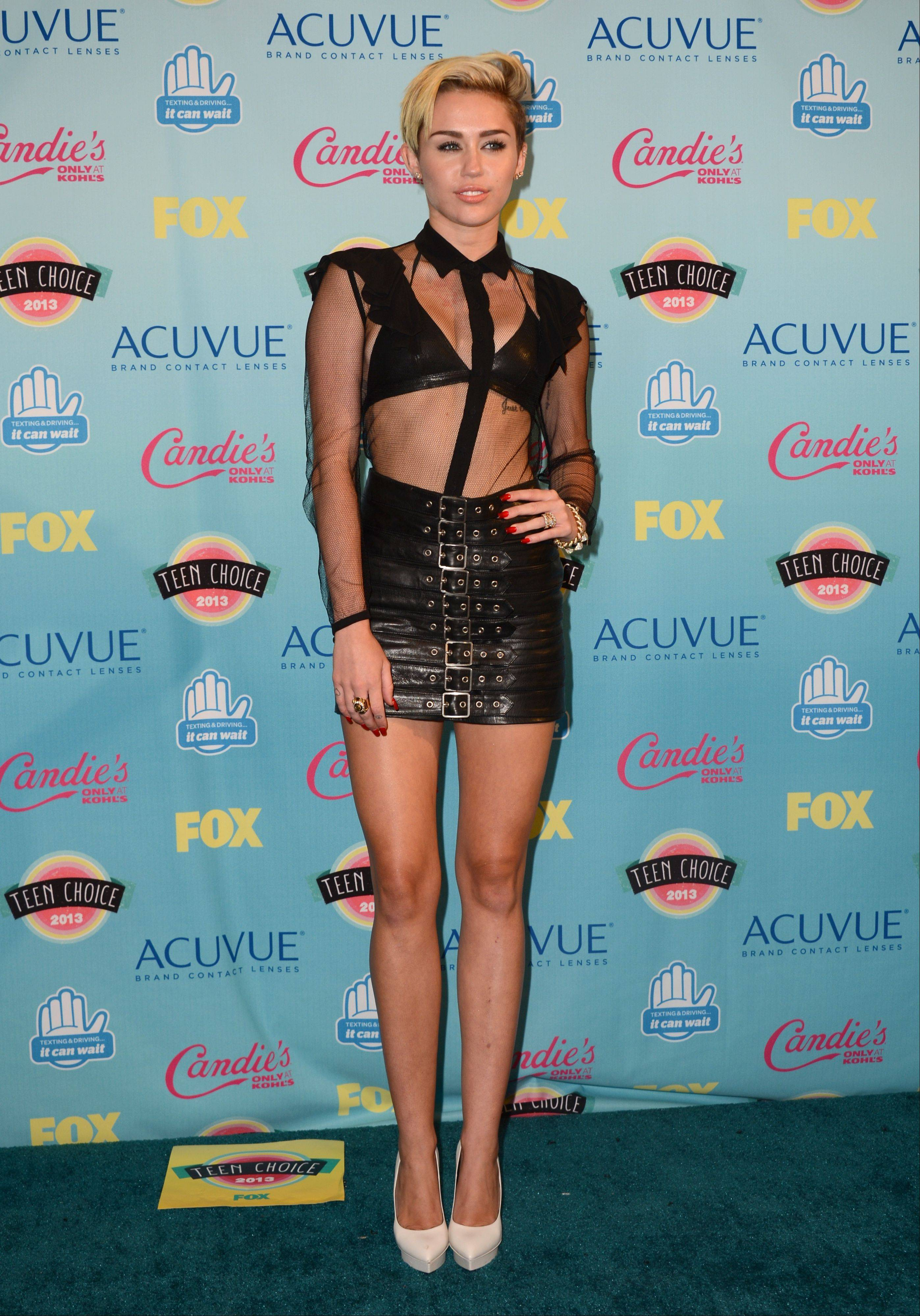 Miley Cyrus poses backstage at the Teen Choice Awards at the Gibson Amphitheater on Sunday, Aug. 11, 2013, in Los Angeles.