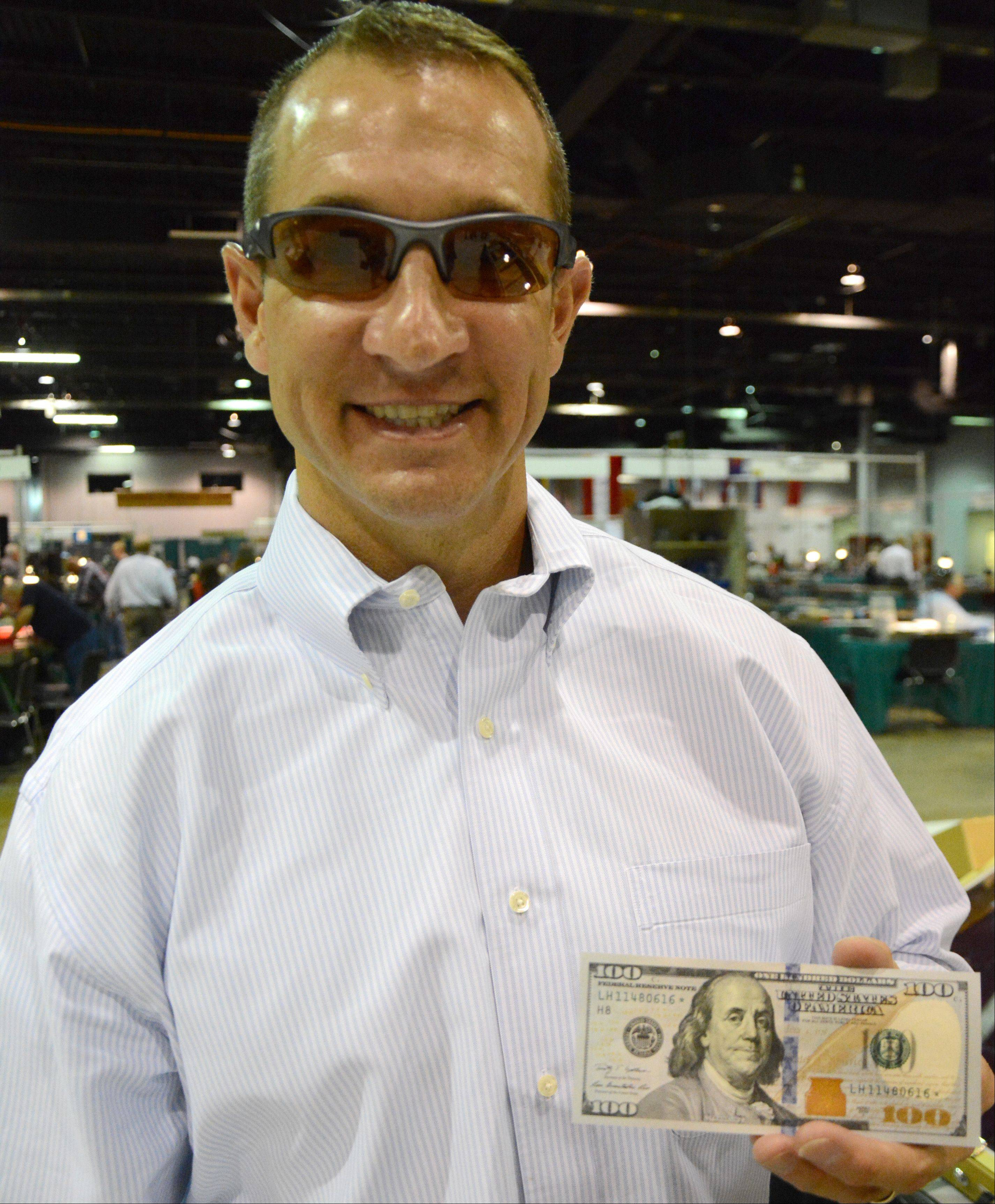 Kevin Brown, marketing manager for the Bureau of Engraving and Printing, poses with the new $100 bill. The bill will be on public display during the World's Fair of Money this week at the Donald E. Stephens Convention Center in Rosemont.