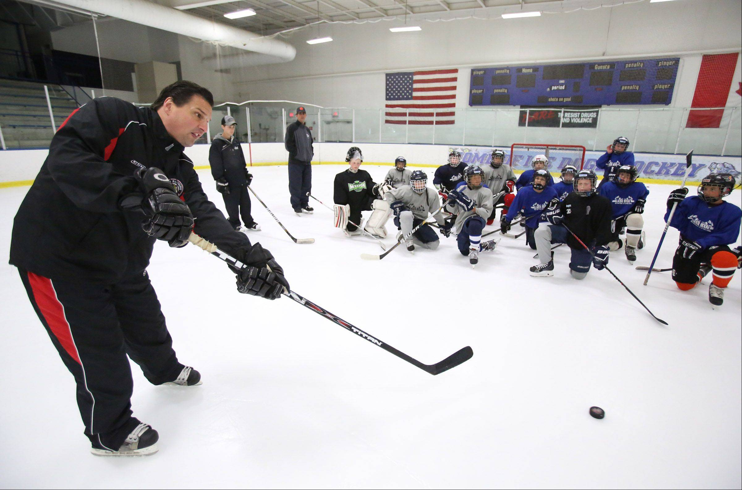 Eddie Olczyk, television color analyst for the Chicago Blackhawks gives passing instruction during a hockey camp at Glacier Ice Arena in Vernon Hills on Friday, August 9, 2013.