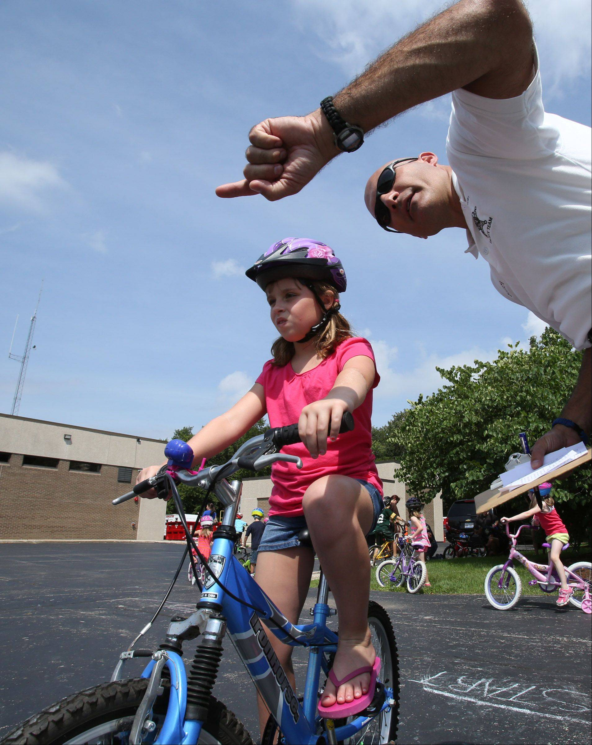 Gurnee police officer Martin Deperte gives riding course instructions to Lindsey Prims, 8, of Gurnee, during a Gurnee Days bike rodeo at Fire Station #1 Friday.