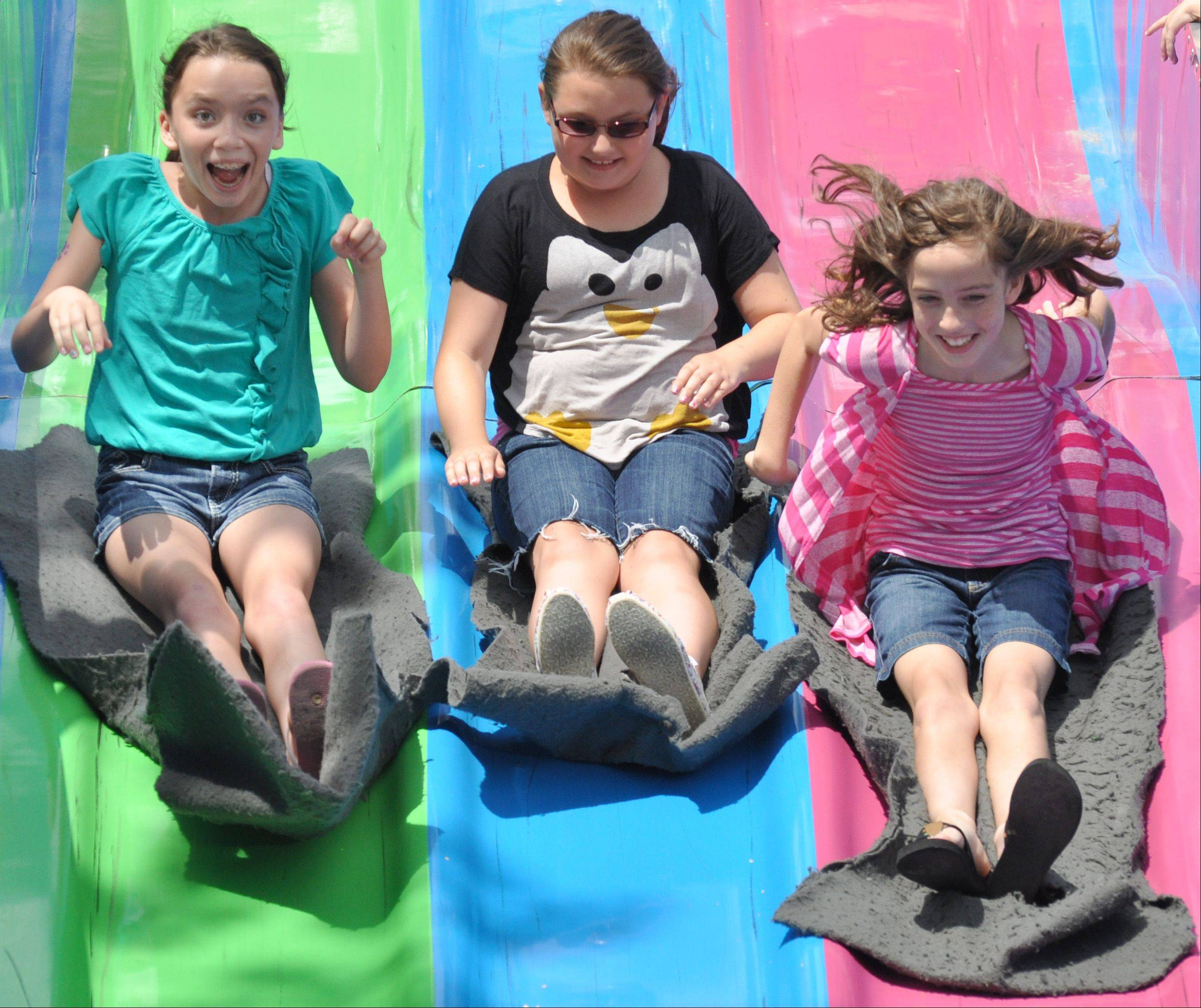 From left, Sarah Hubbartt, Jessica Jablonowski, and Caroline Hubbartt, all of Gurnee, ride down the Fun Slide during Gurnee Days Saturday.