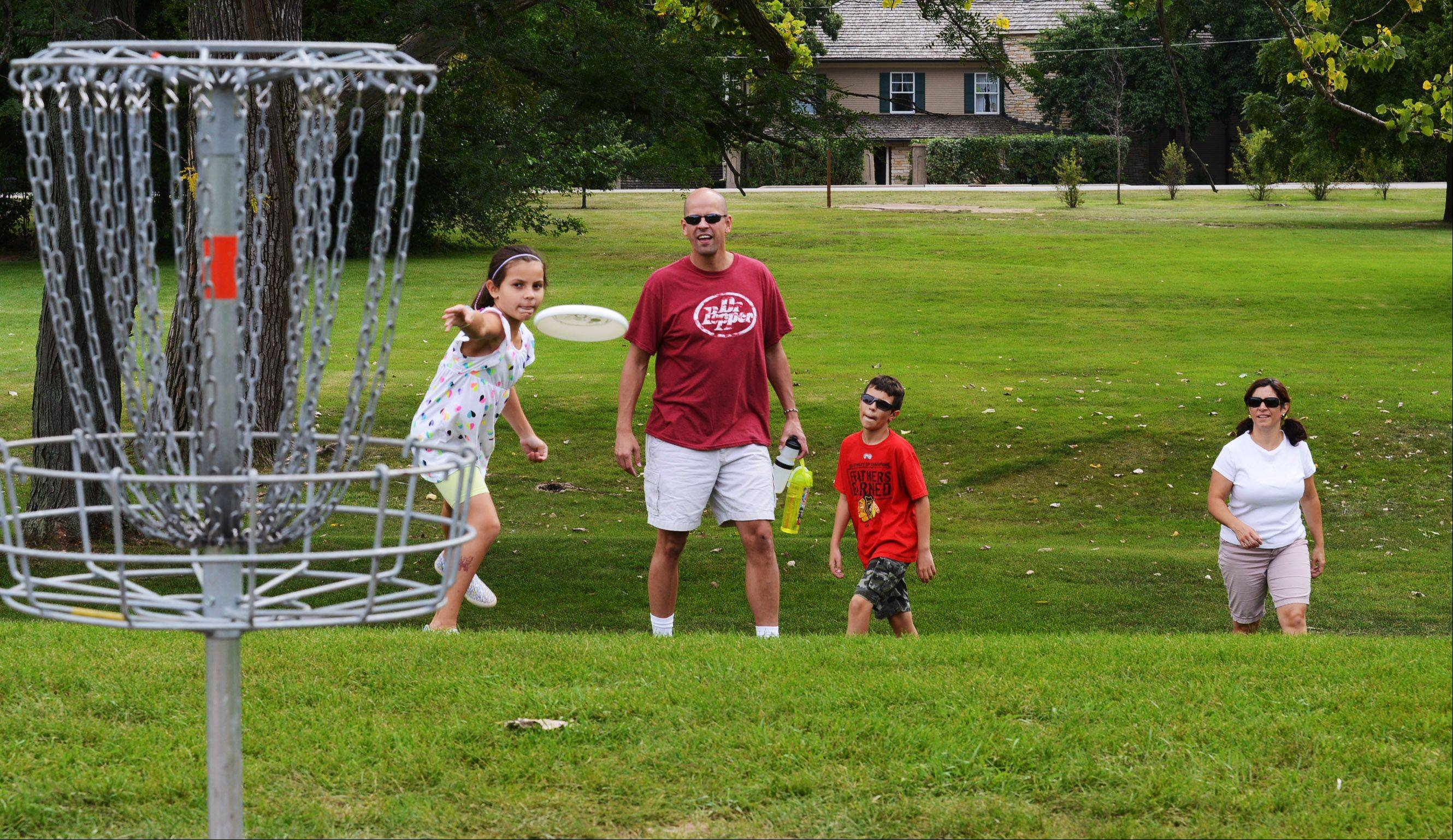 The Disk Golf Course was a popular stop in Wheeler Park in Geneva Sunday. Avery Lundblad, 8, sends a disk towards a basket while Dad Brad, Brother Xander, 12, and Mom Cathy watch and wait their turn. They are from Geneva.