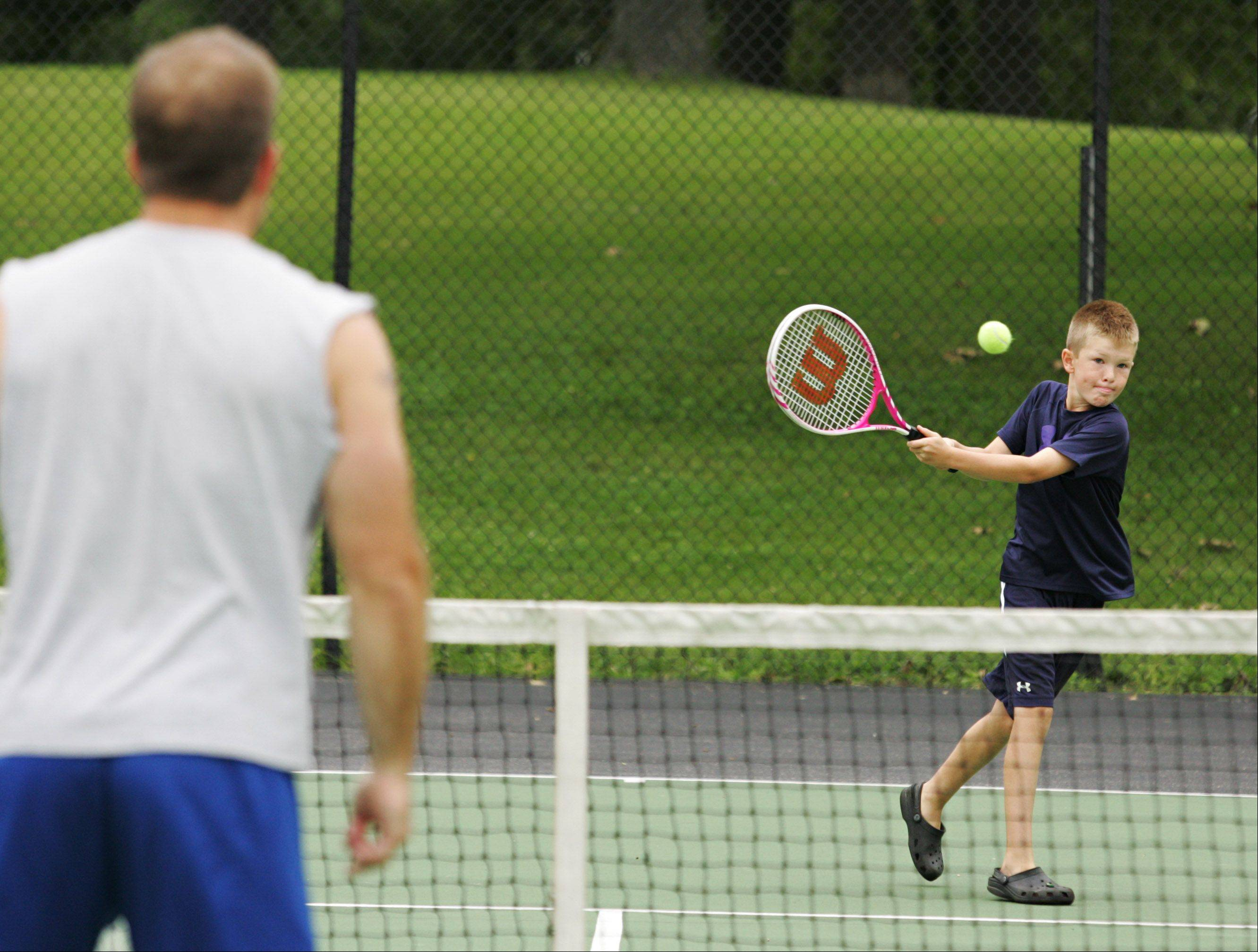 Matthew Wrzala, 10, hits a backhand to his dad, Keith as they play tennis at Ralph Seyller Park Monday morning in Hampshire. Matthew had asked to play tennis with his dad, so they got out to play before the wet weather arrived later in the day.