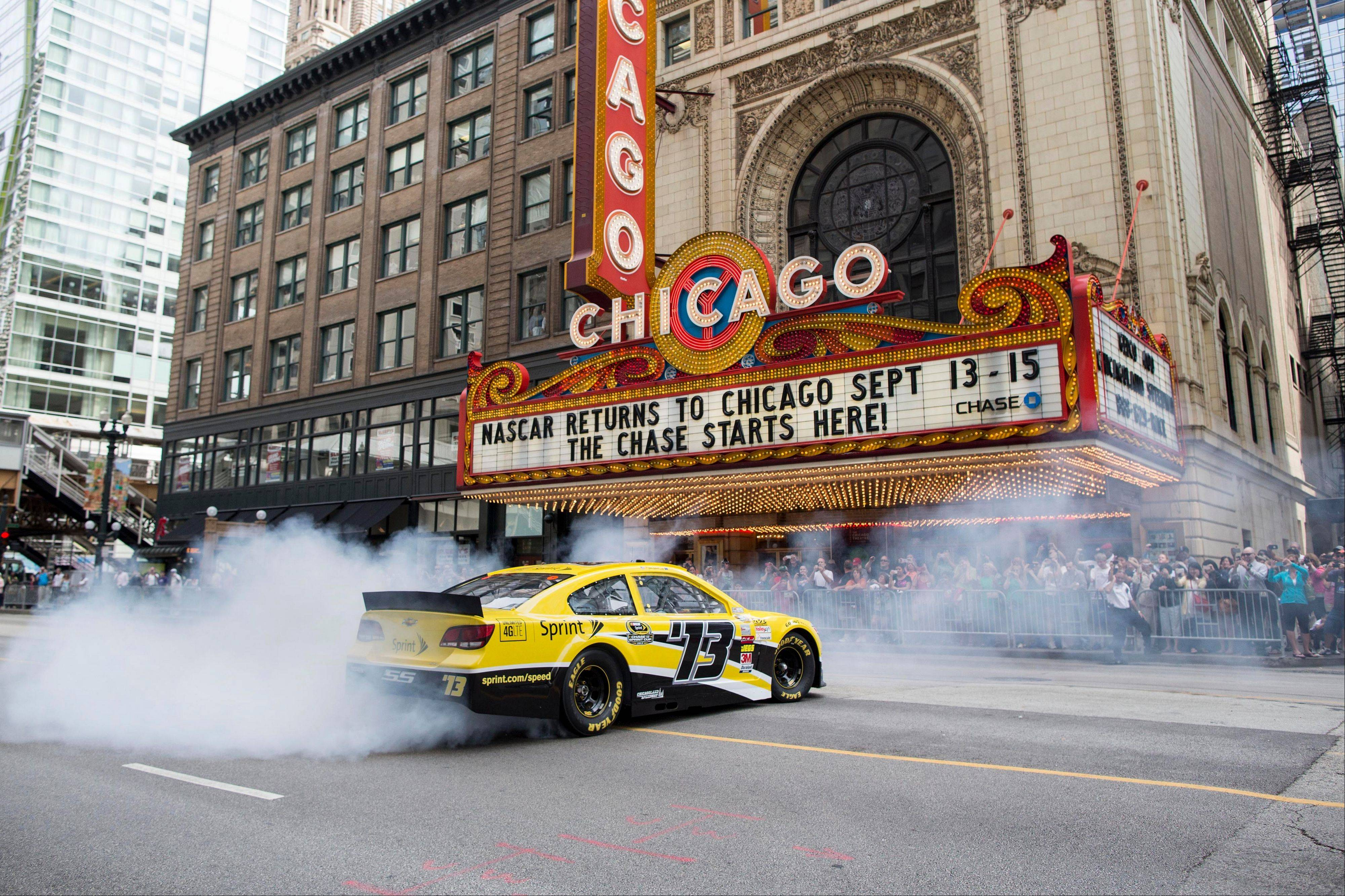 Dale Earnhardt Jr. performs a burnout Monday morning in front of the Chicago Theatre in Chicago.