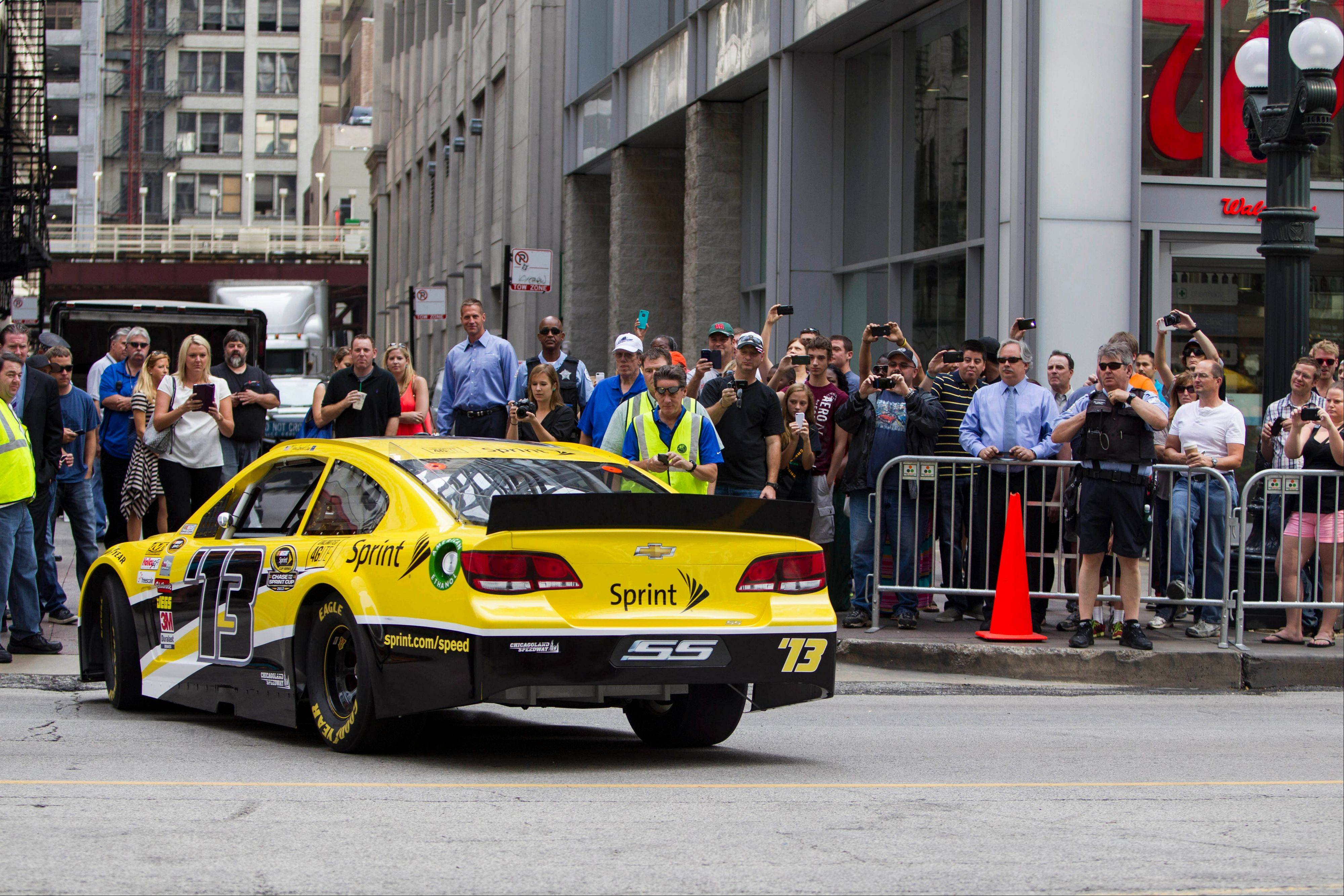 Fans take photographs as Dale Earnhardt Jr. backs out of a street before performing a burnout Monday in front of the Chicago Theatre.