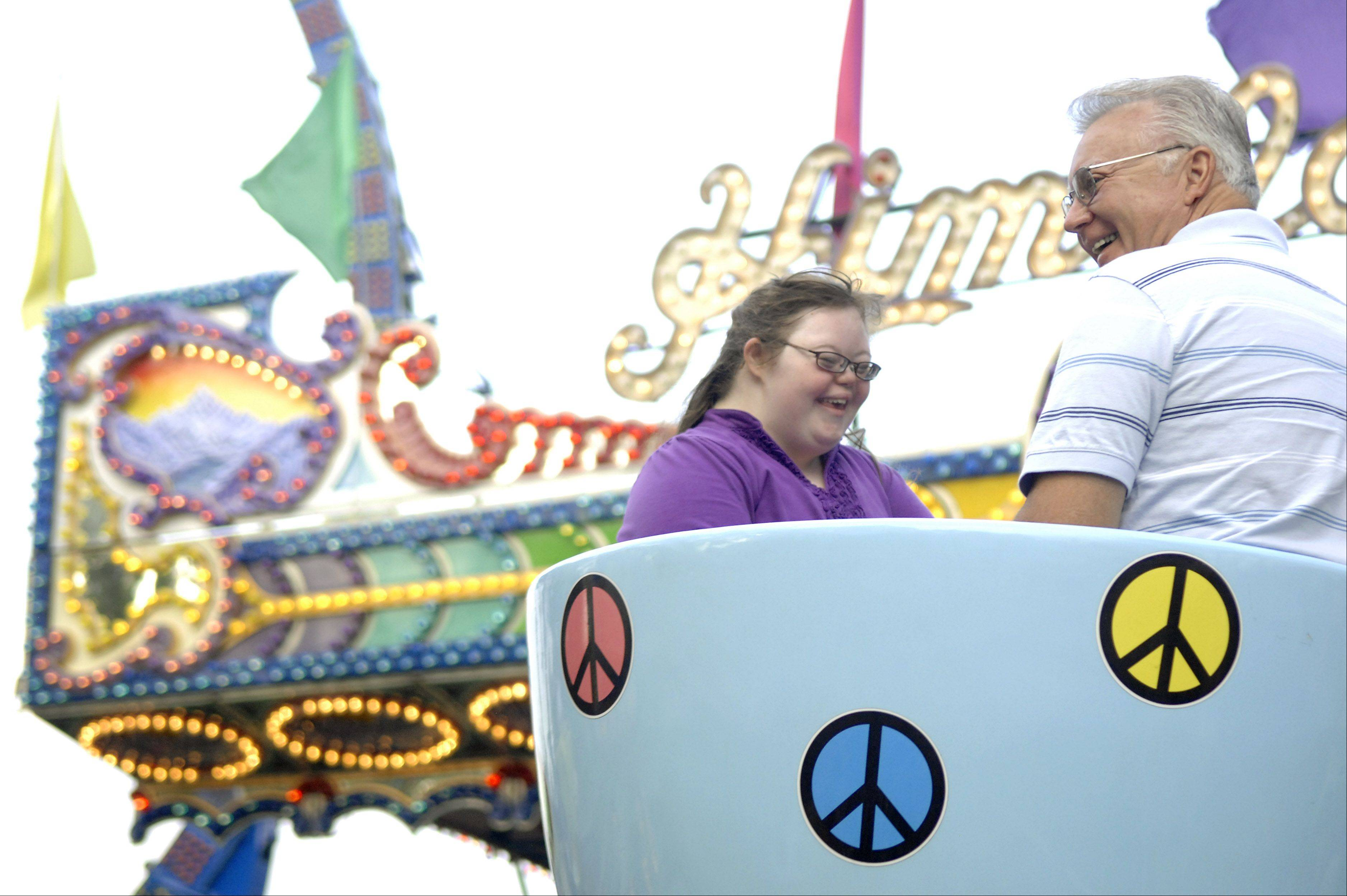 "Mikayla Nicholas, 12, of Sycamore takes a ride on the teacups with her grandfather, Jim Kozar of Burlington, during ""A Special Night for Special Kids"" at South Elgin's RiverFest Express."