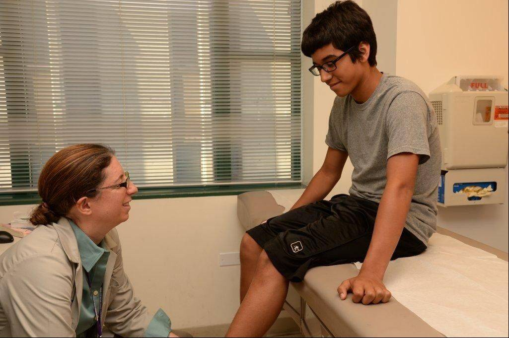 Dr. Rebecca Carl, pediatric sports medicine physician at Ann and Robert H. Lurie children's Hospital of Chicago, examines Ethan Valenciana, 12, of Chicago.