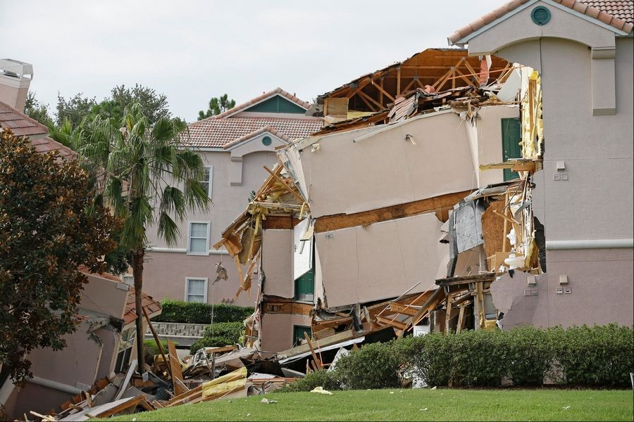 Damage to buildings caused by a sinkhole 40 to 50 in diameter is seen at the Summer Bay Resort, Monday.