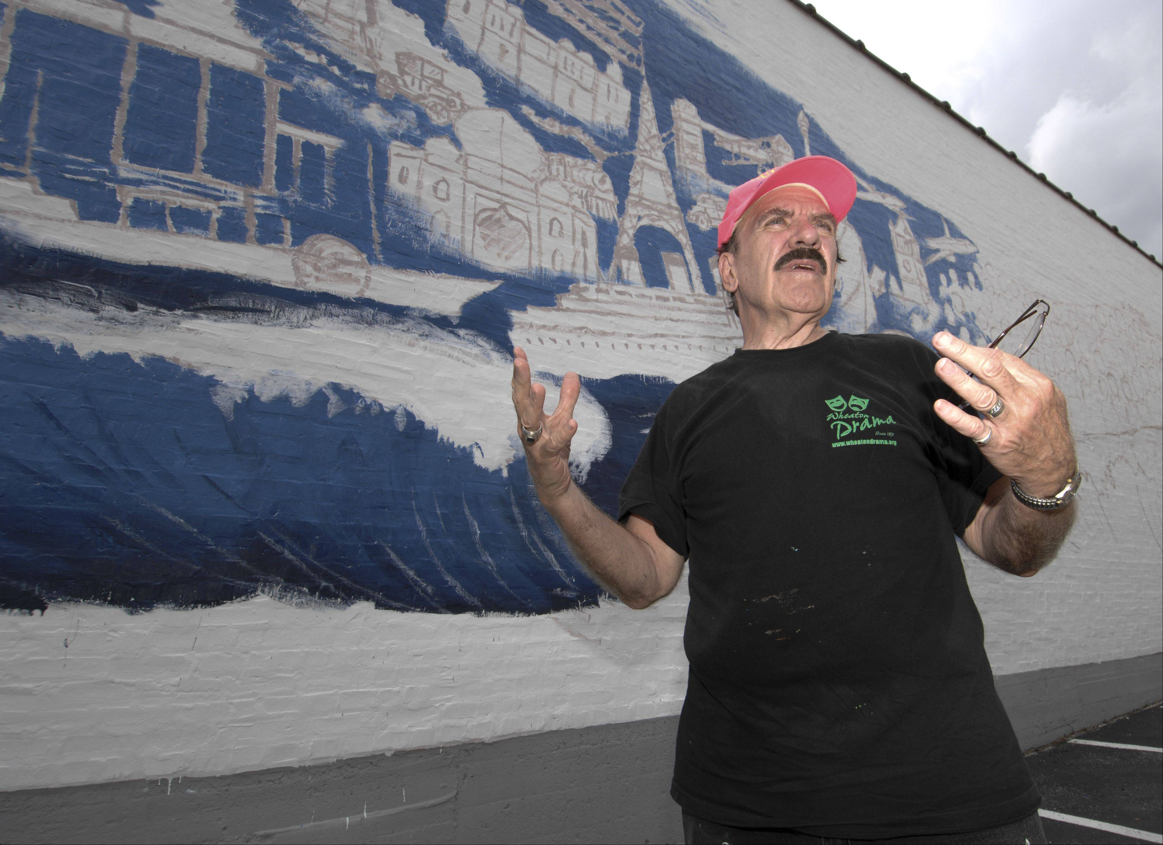 "Artist R.J. Ogren works on his mural, ""Pearls of the Universe,"" on a wall at 1026 College Ave. in Wheaton. Inspired by a poem by Wheaton resident Mehret Asgedo"