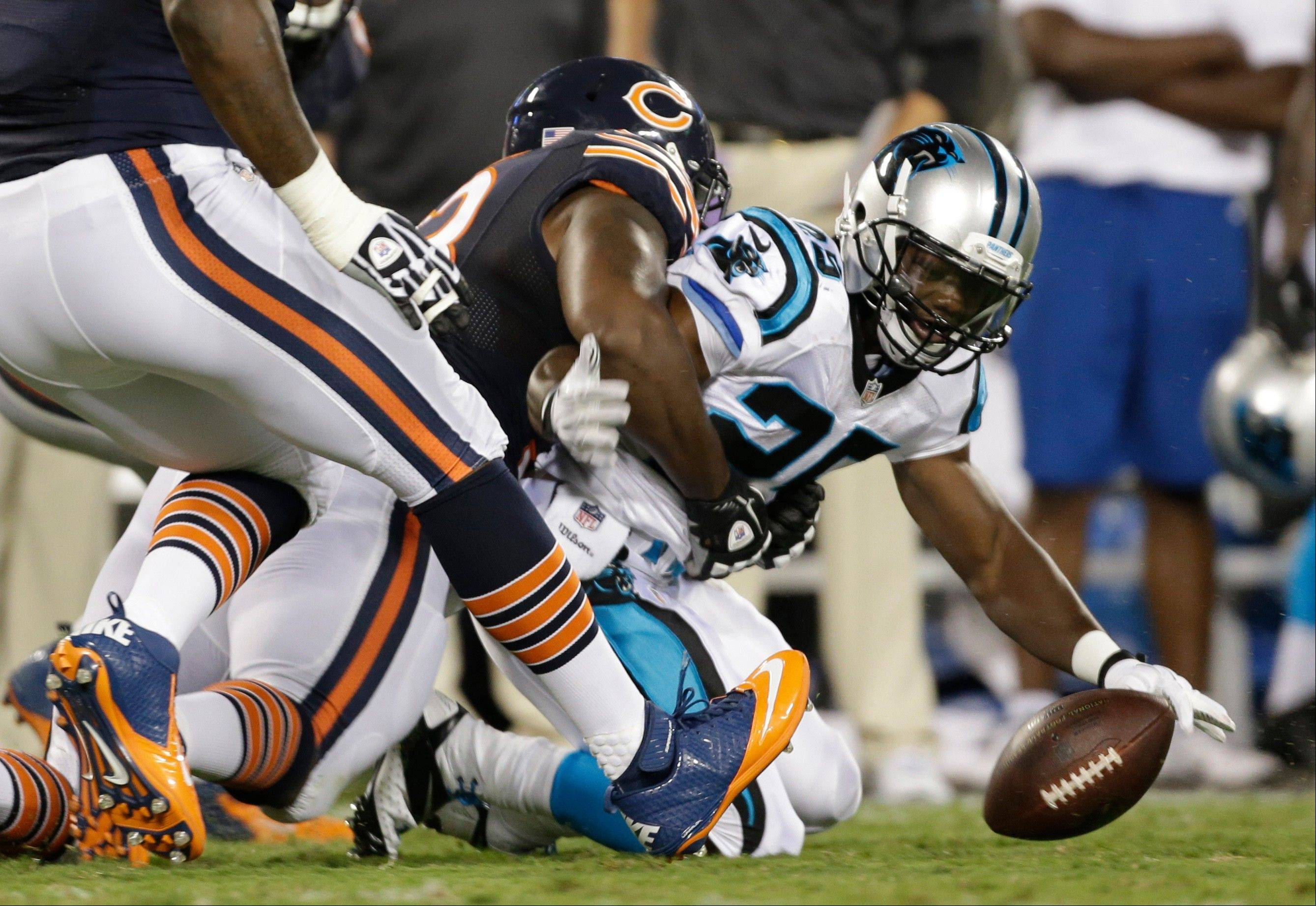 Carolina Panthers' Kenjon Barner, right, fumbles the ball after being hit by the Bears' Nate Collins, left, during the first half of a preseason NFL game in Charlotte, N.C., on Friday, Aug. 9, 2013. The Bears recovered the ball.