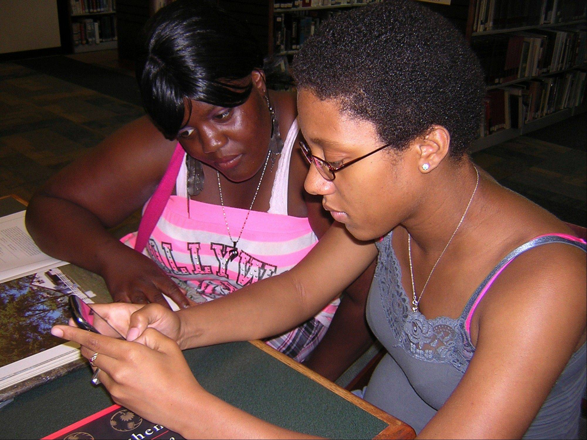 Samone Johnson, 19, of Alvin, types a text on her cell phone next to Zion Moses, 20, left, of Danville at the Danville Public Library. Studies show younger children are getting their own cell phones.