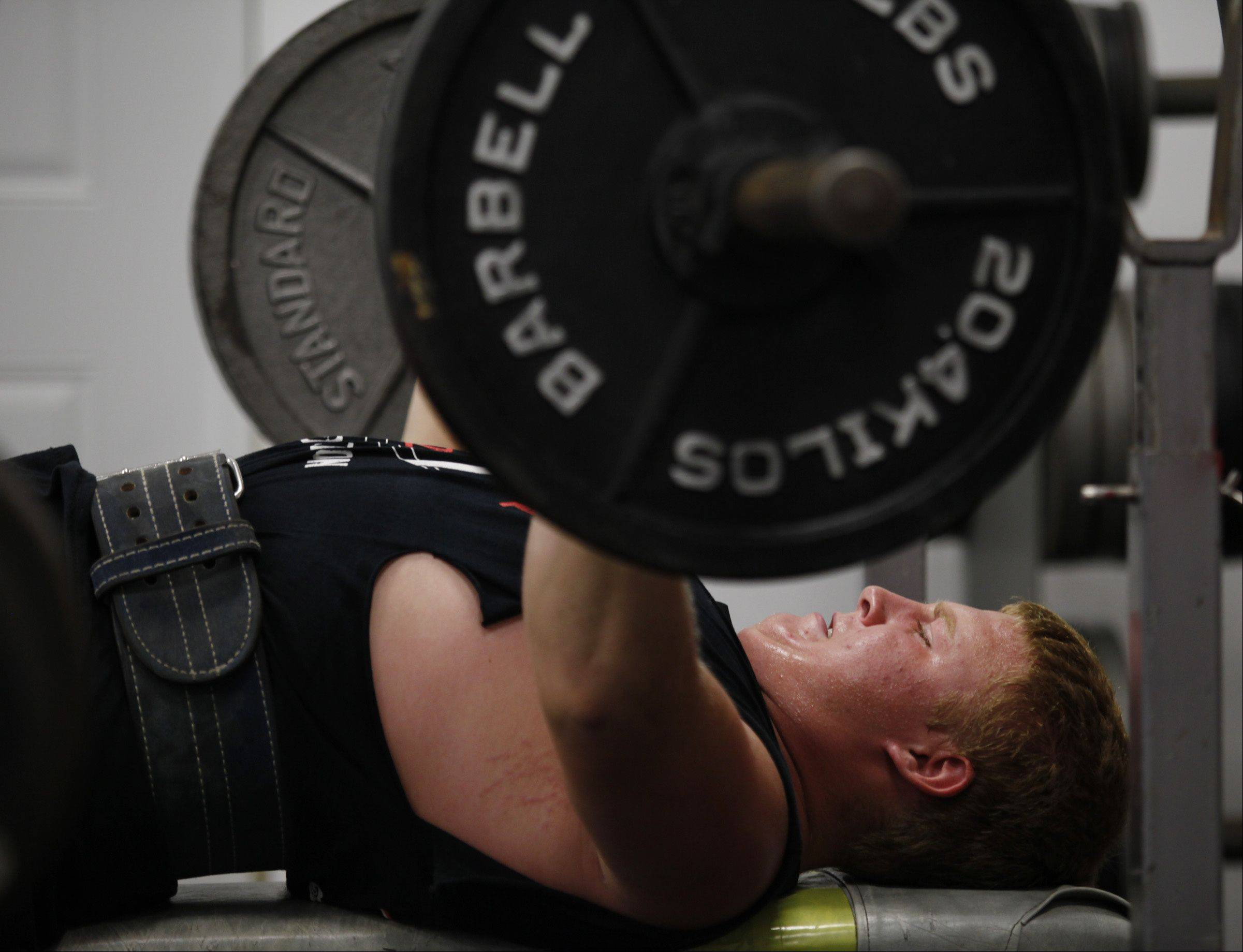Dominic Swanson, a sophomore at Huntley High School, is heading to Prague in October to compete in a powerlifting competition. Here he bench presses 225 pounds during a workout at his Union home.