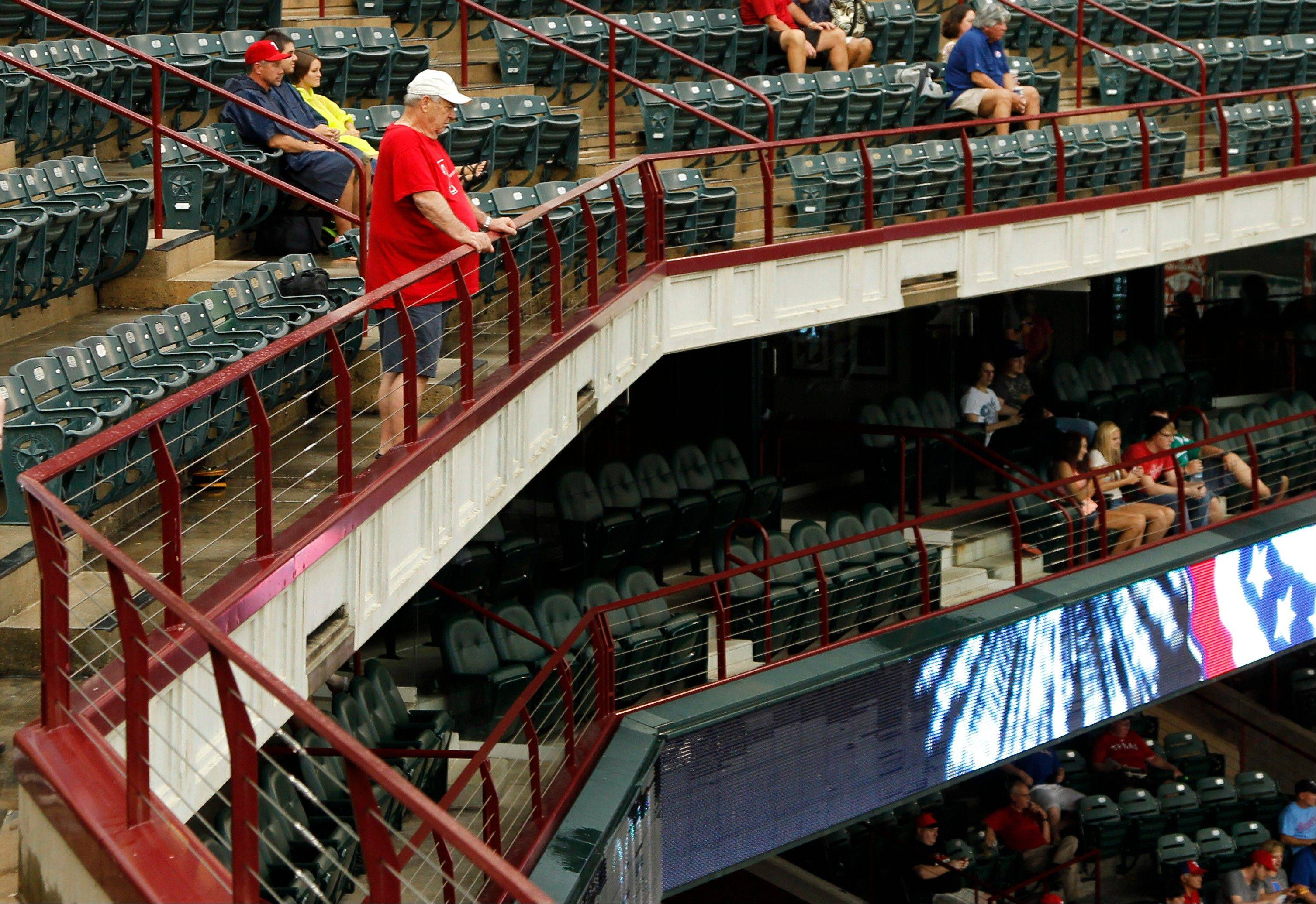 A fan stands on the clubhouse level of Rangers Ballpark in Arlington, Texas, on Tuesday. In 2011, a fan died there in fall from the left-field seats.