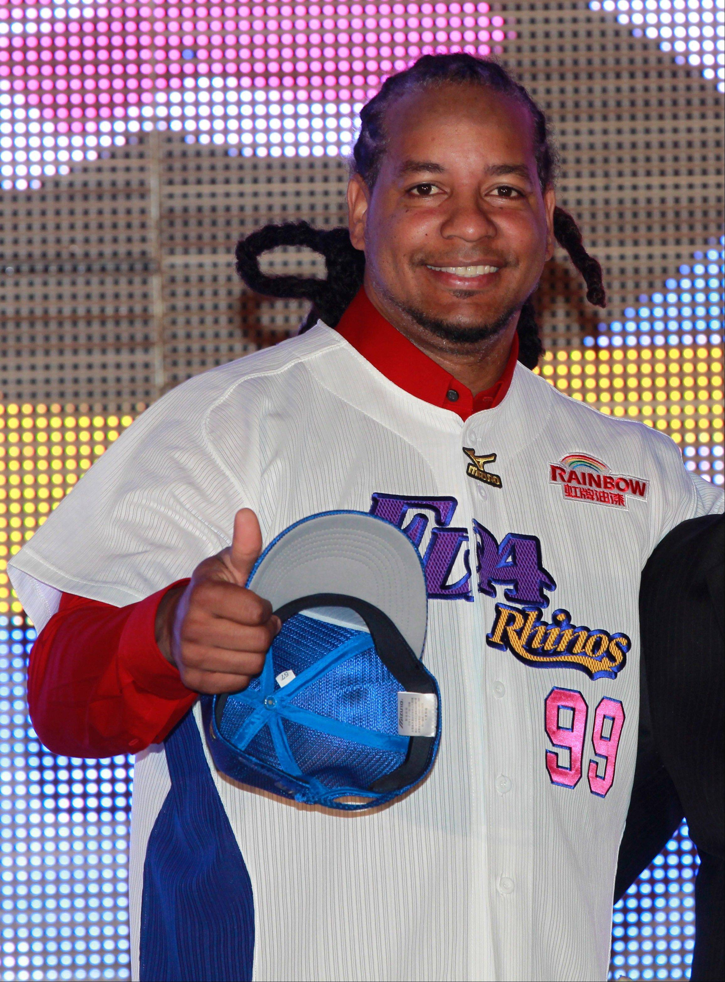 Manny Ramirez poses in his new jersey after signing a short-term contract to play on the EDA Rhinos in Taiwan�s professional baseball league this spring. Ramirez was released from his minor league contract Tuesday by the Texas Rangers.