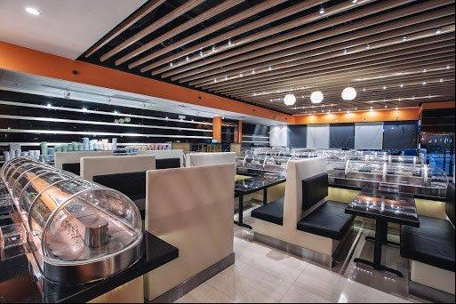 Japanese food arrives at tables via a refrigerated conveyor belt at Sushi +, now open in Aurora.