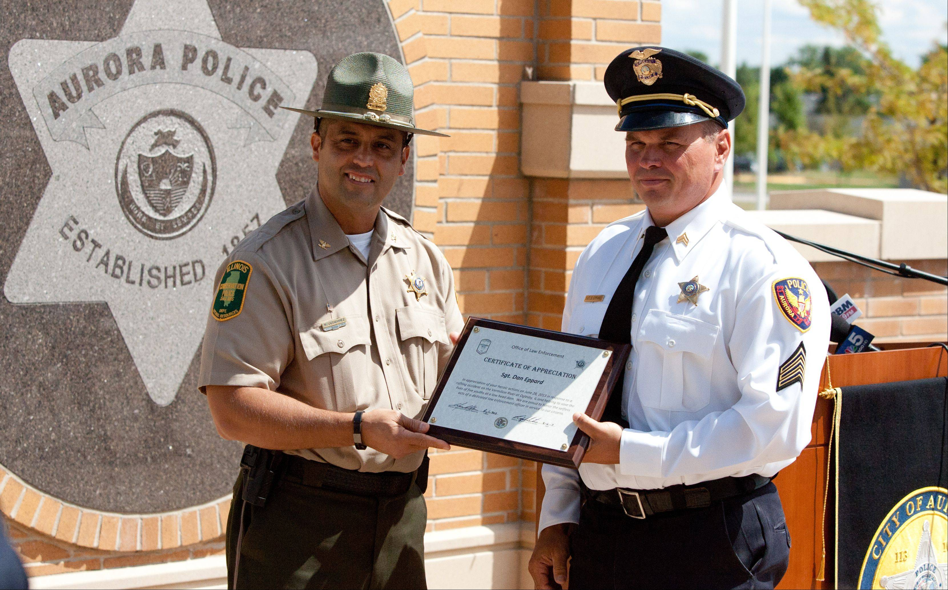 Illinois Conservation police Director Rafael Gutierrez, left, recognizes Aurora police Sgt. Daniel Eppard for his work with Sgt. Rick Ahlgren to pull five boys to safety from a dam along the Vermilion River.