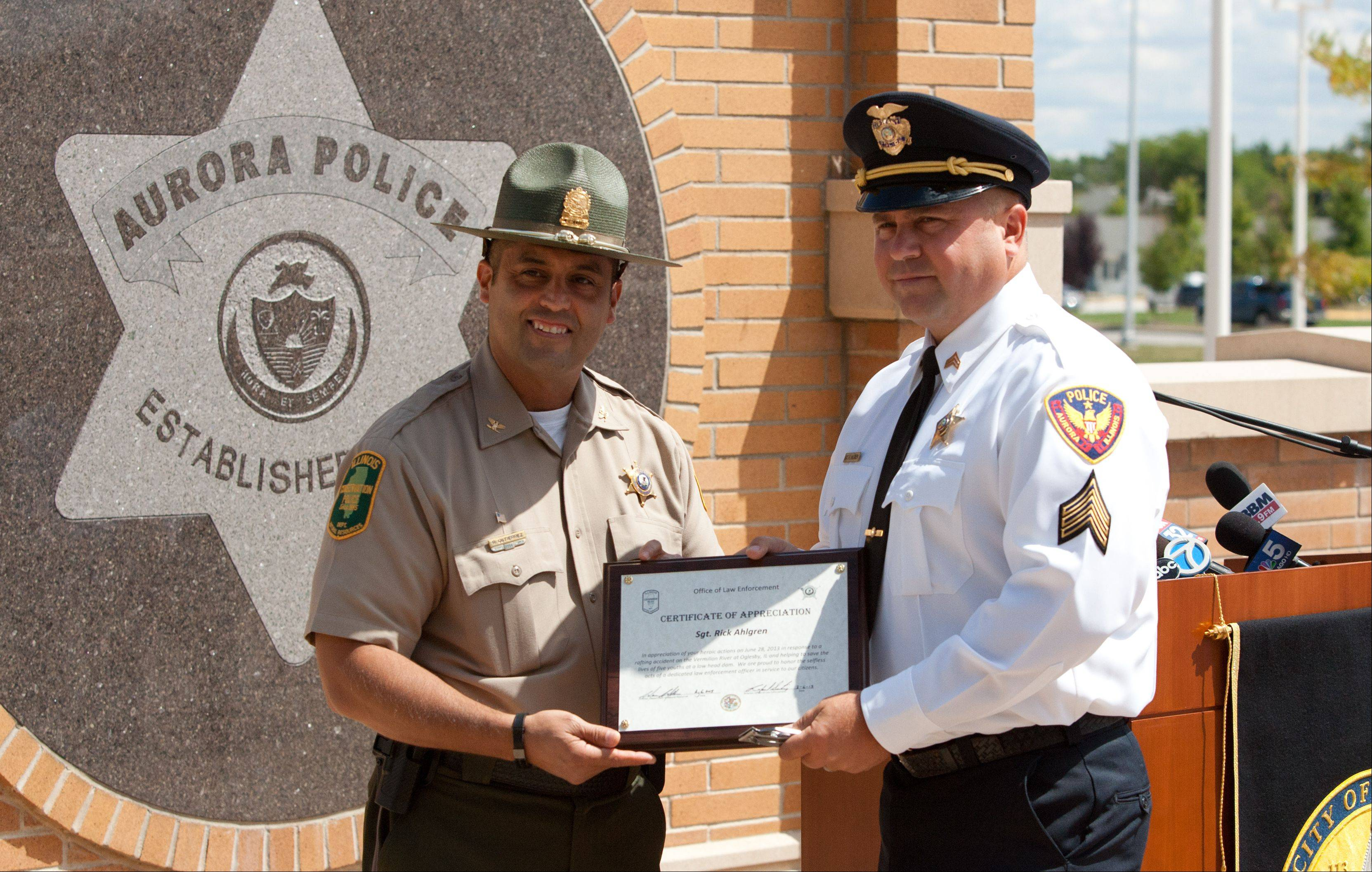 Aurora police Sgt. Rick Ahlgren, right, is recognized Tuesday for his work with Sgt. Daniel Eppard in pulling five boys to safety from a dam along the Vermilion River.
